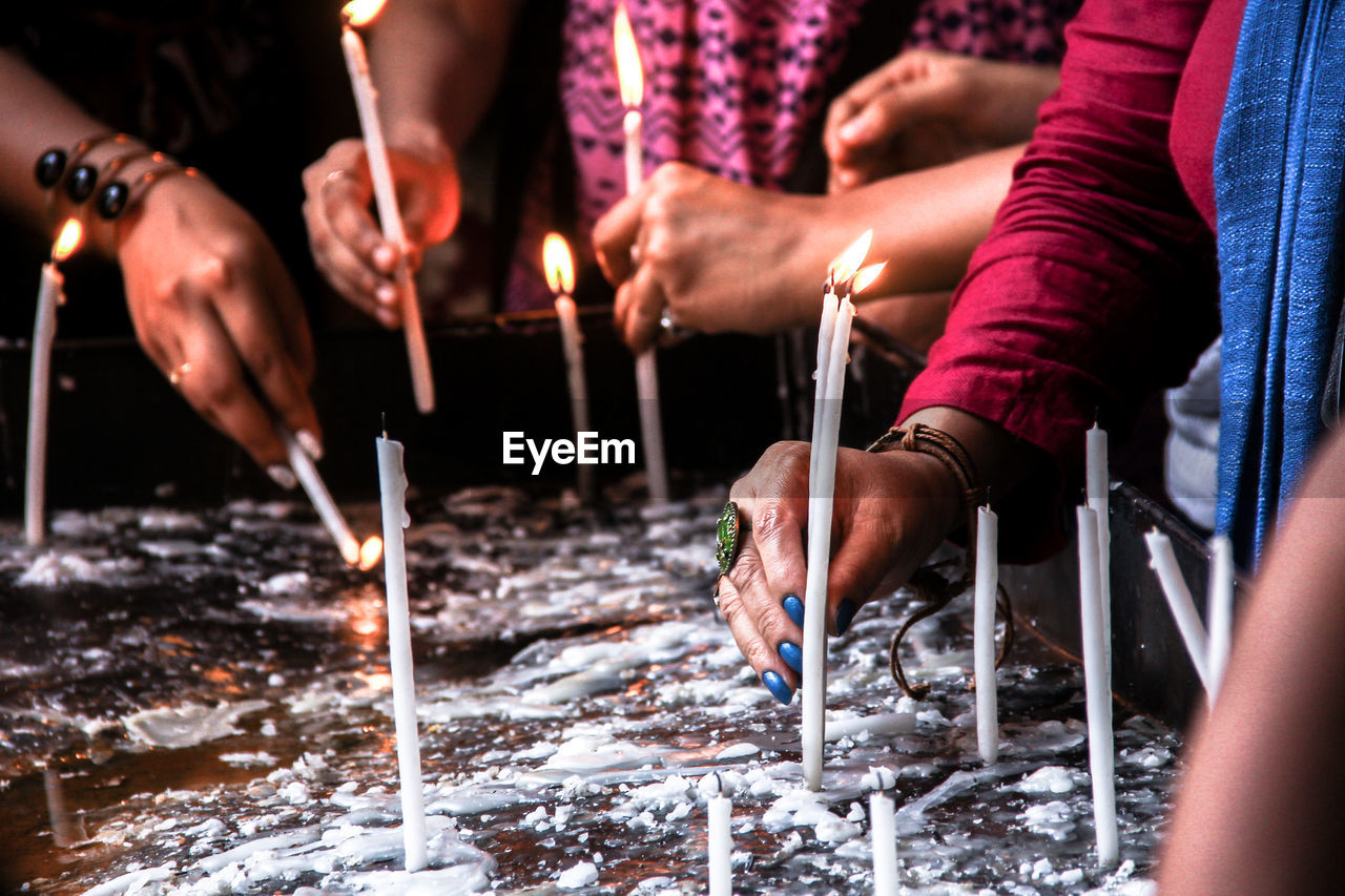 Close-Up Of Hands Holding Candles