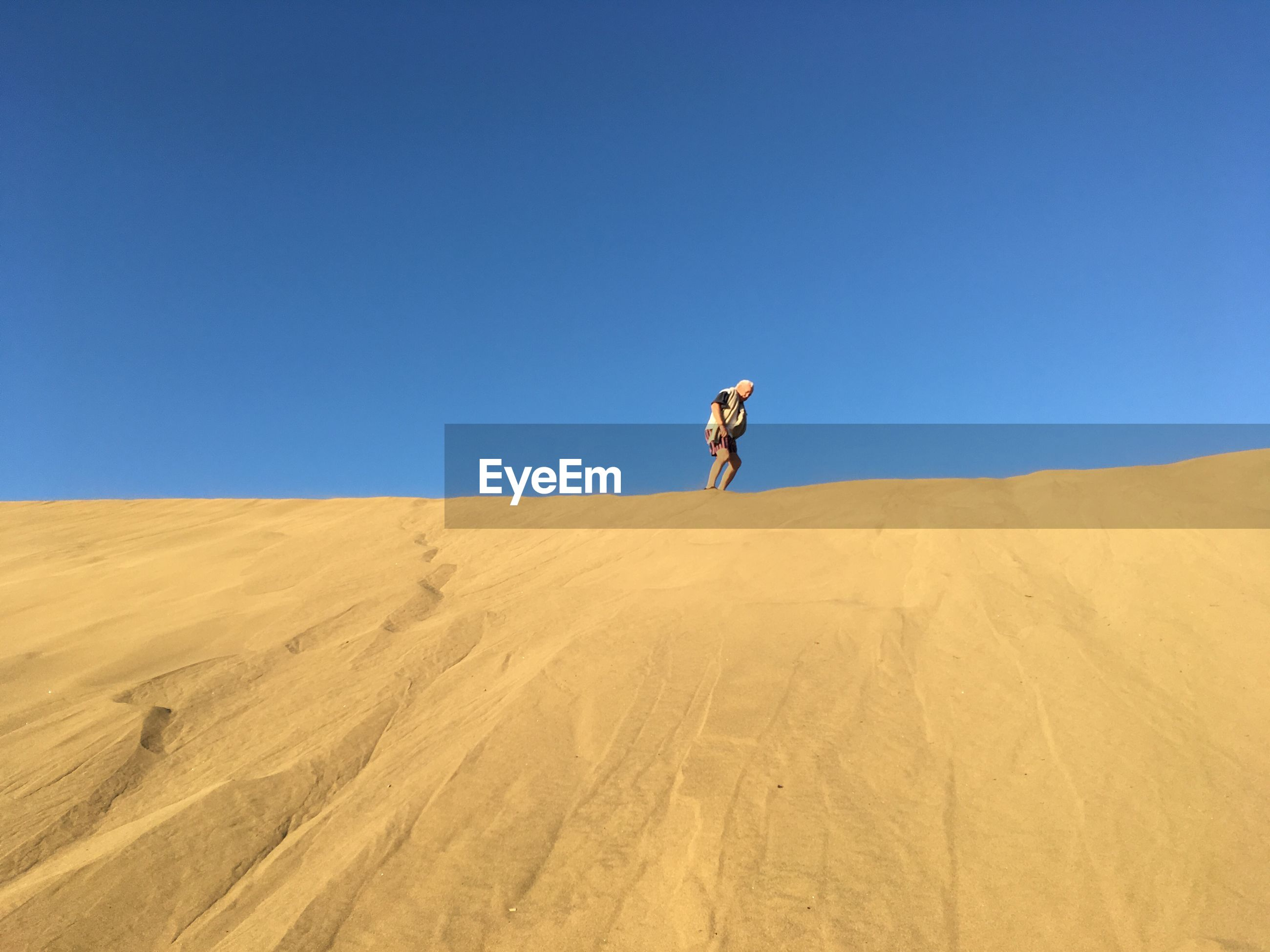 Low angle view of mature man standing at desert against clear blue sky