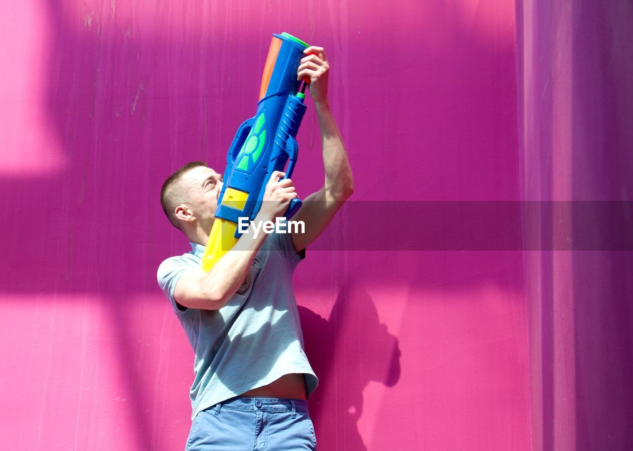 Man Aiming With Squirt Gun Against Pink Wall