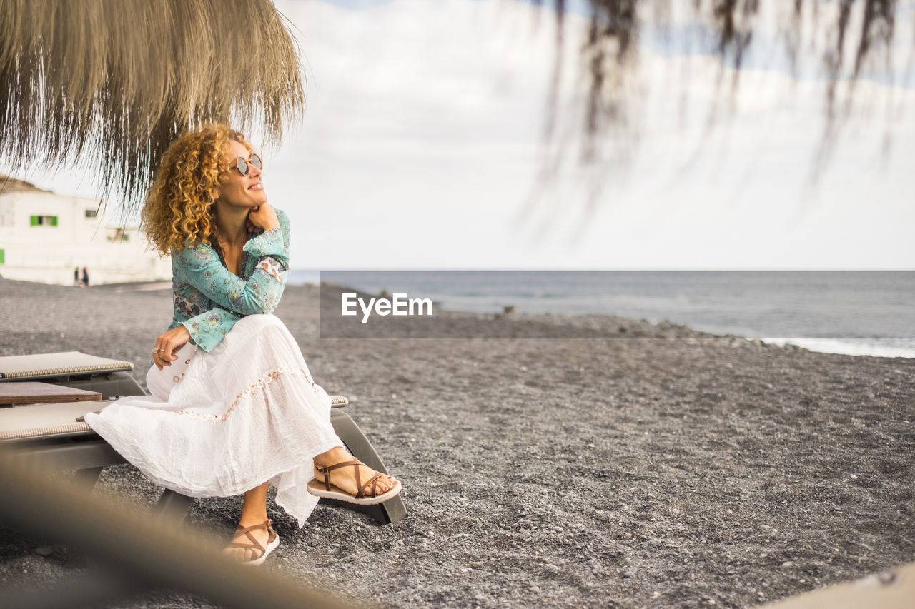Smiling woman looking at sea while sitting on lounge chair