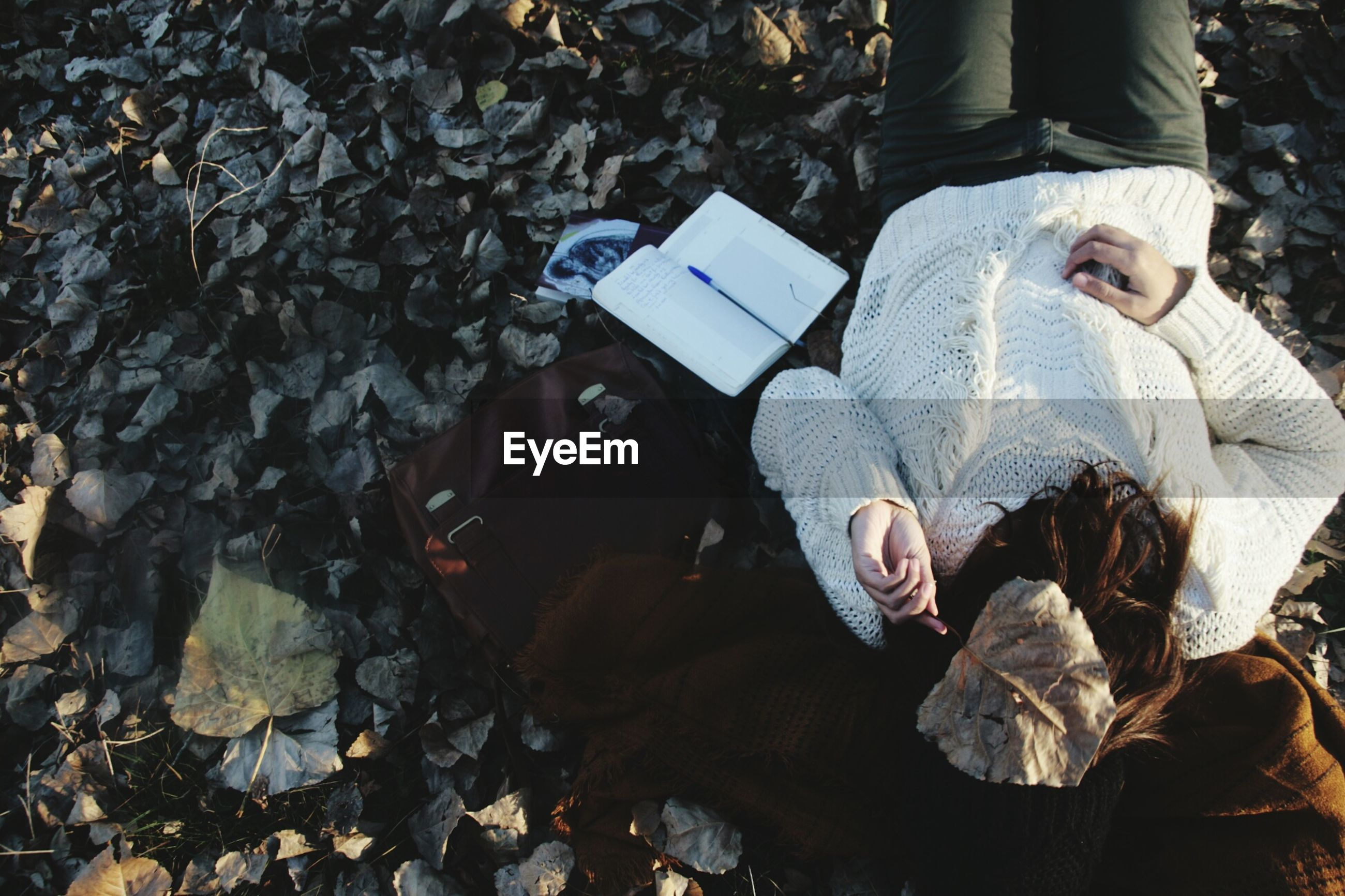 High angle view of woman covering face while lying by books on stones