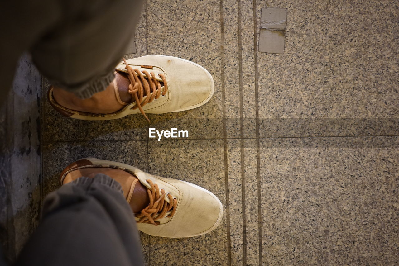 low section, shoe, human body part, body part, human leg, one person, real people, lifestyles, high angle view, men, personal perspective, standing, casual clothing, women, leisure activity, day, adult, human foot, selective focus, flooring, outdoors, human limb, tiled floor, jeans