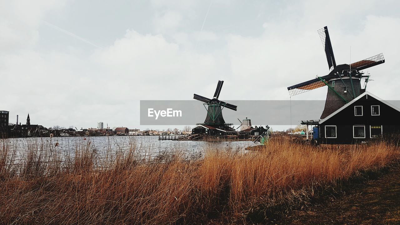 Traditional windmills by lake against sky