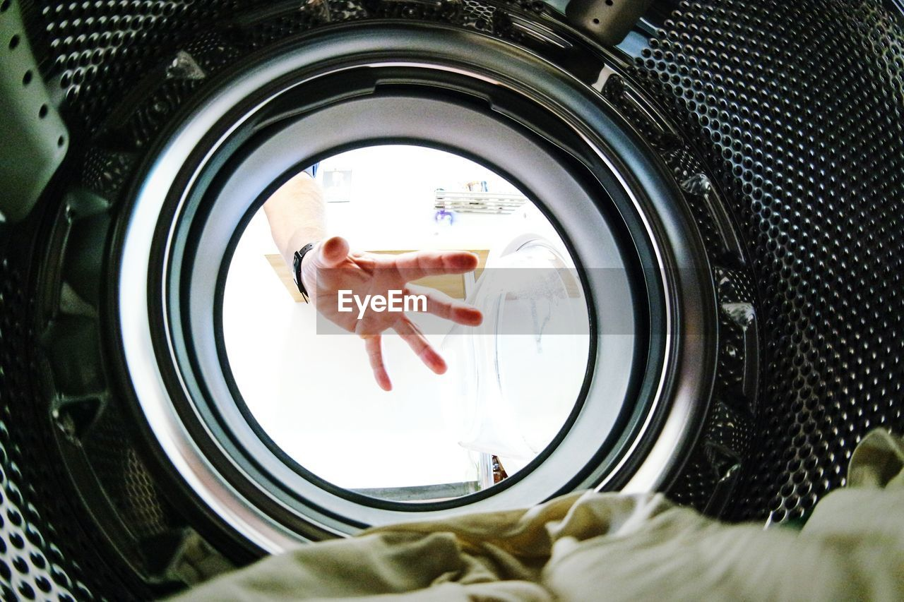 Cropped Image Of Hand On Washing Machine Glass
