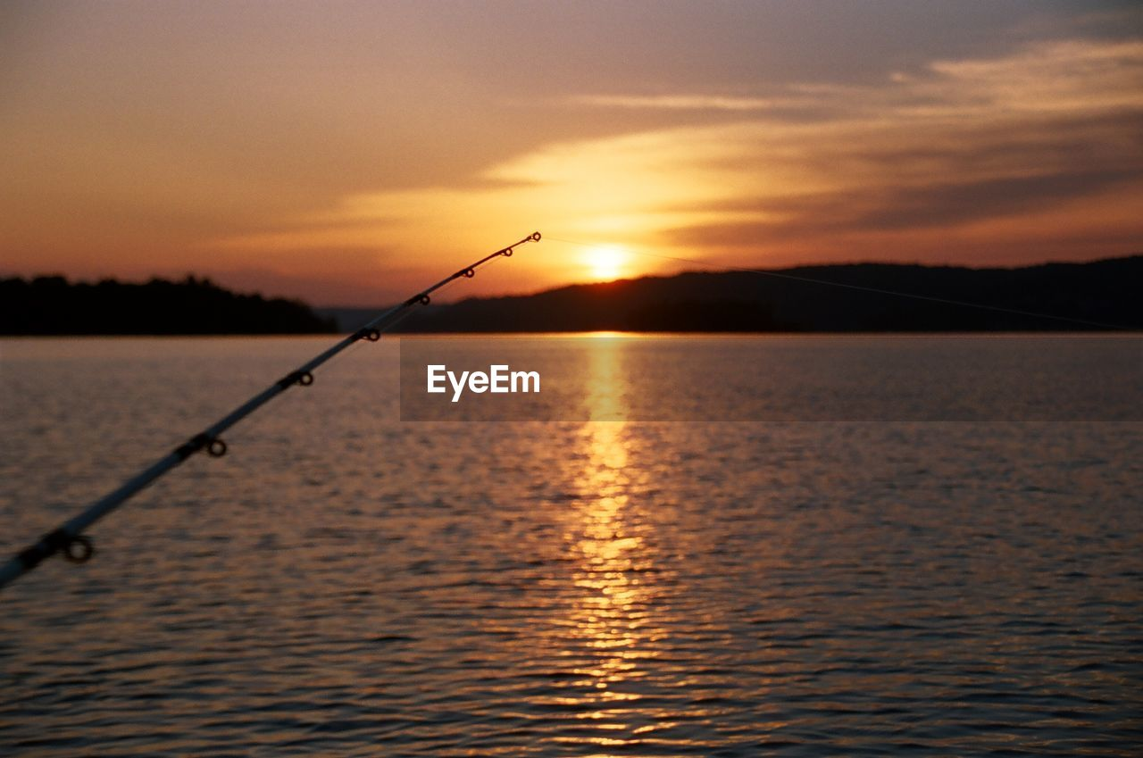 Close-up of fishing rod over lake against sky during sunset