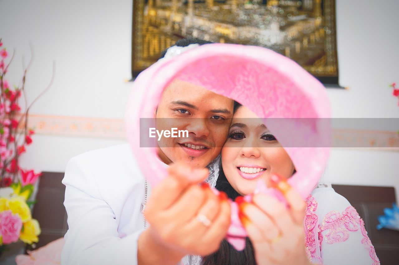 Portrait of smiling couple looking through pink decoration