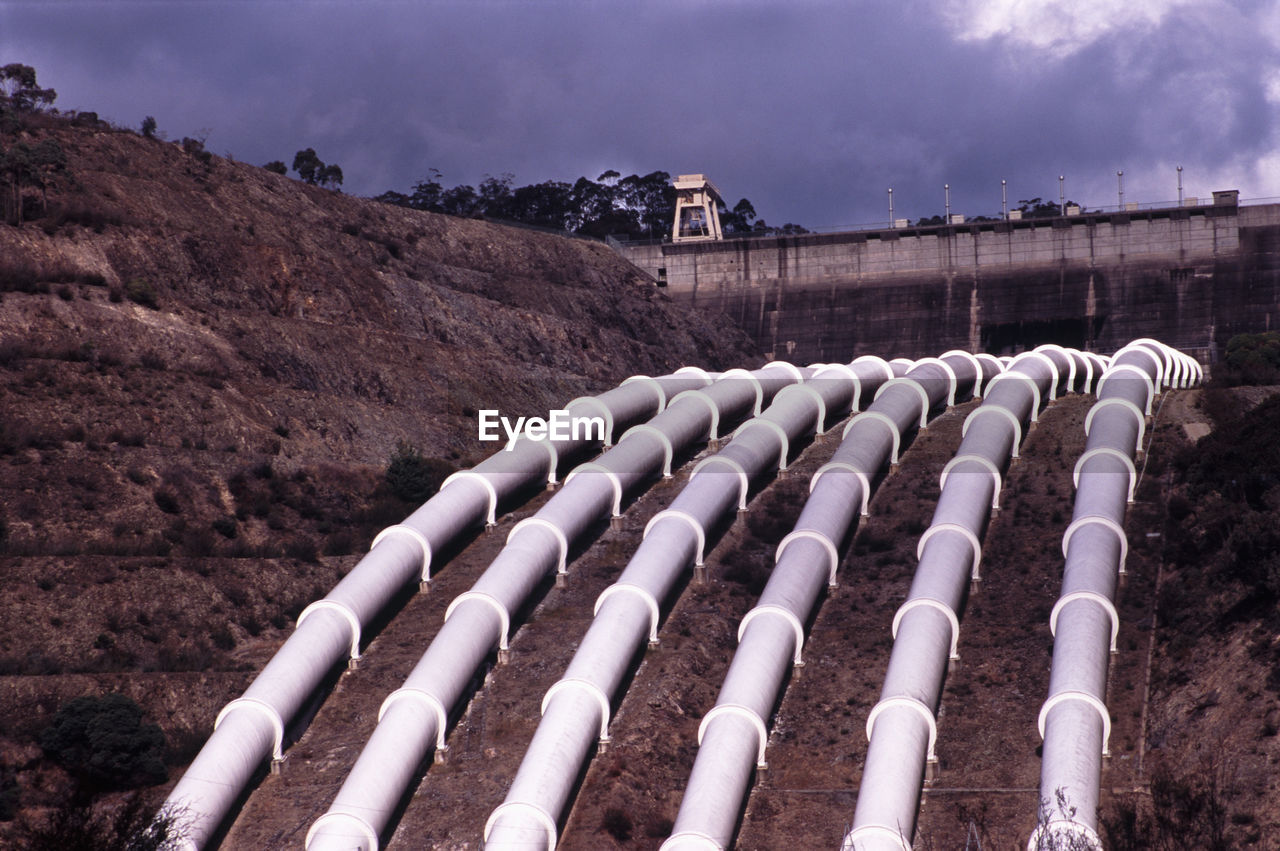 Pipelines on mountain against cloudy sky
