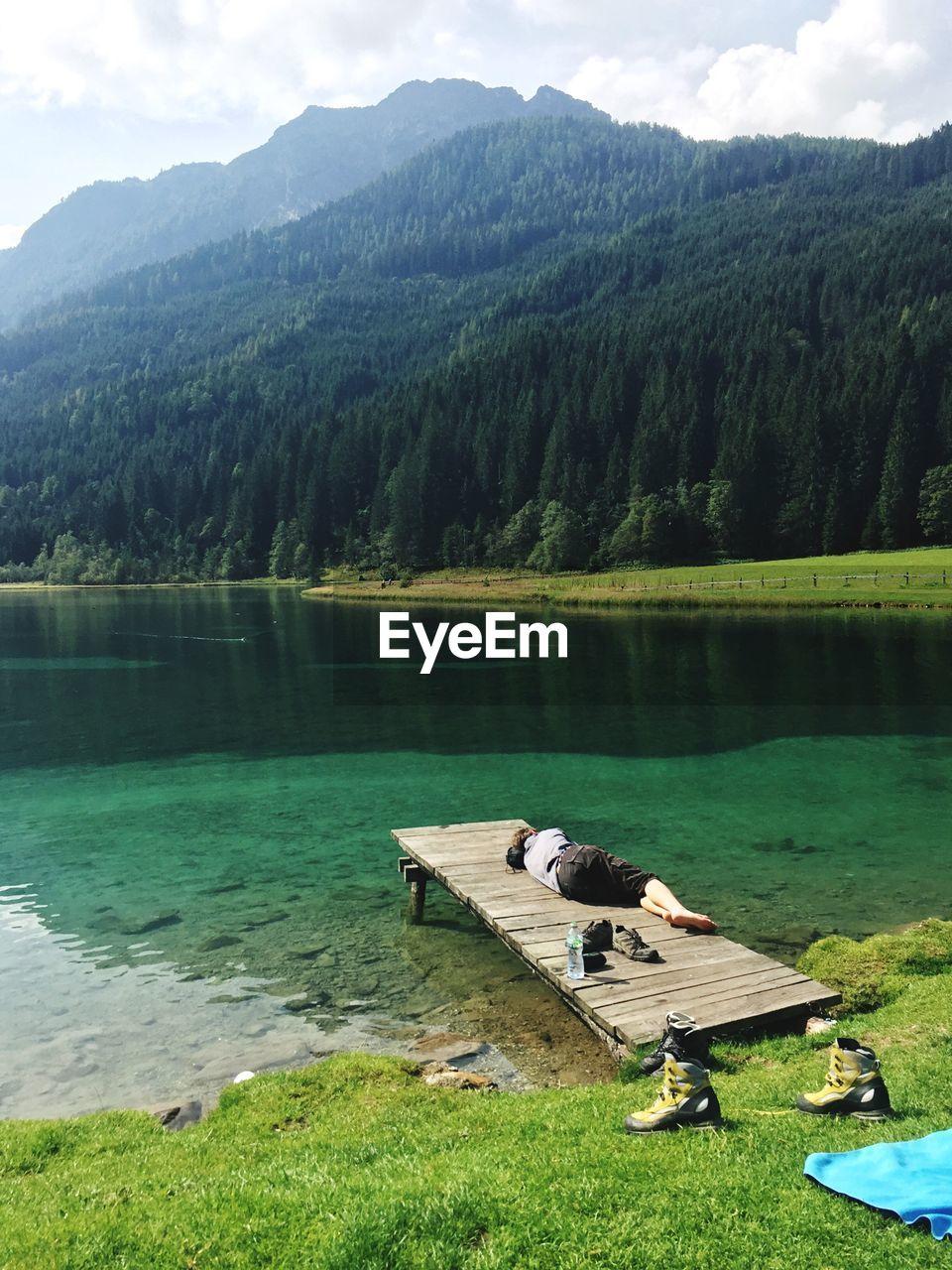 Full length of man sleeping on pier over lake against mountains