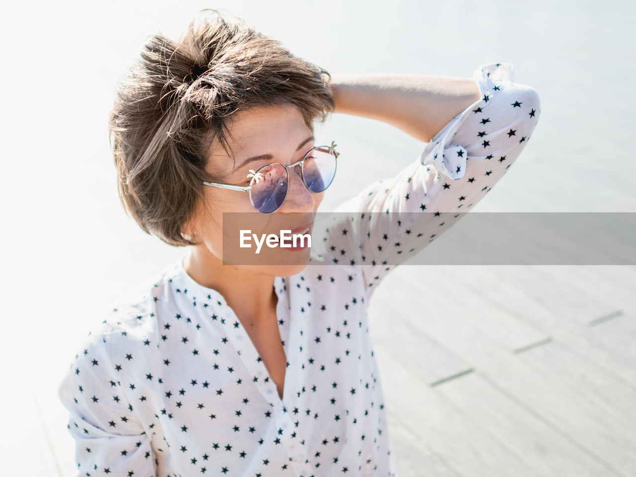 Wind ruffles short hair of freckled woman in colorful sunglasses. smiling woman. summer vibes.
