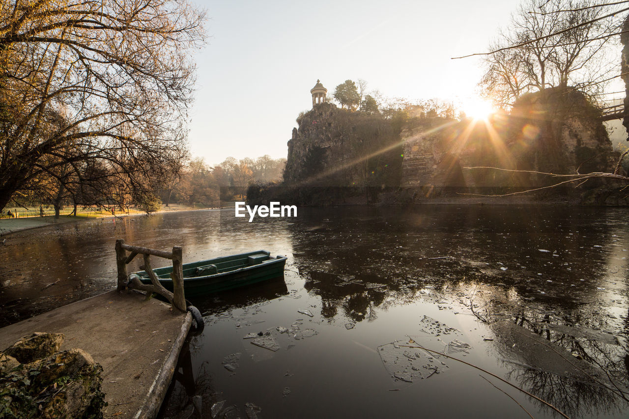 lens flare, water, tree, sunlight, architecture, built structure, river, sun, no people, sky, bare tree, nature, building exterior, outdoors, beauty in nature, sunset, day, clear sky