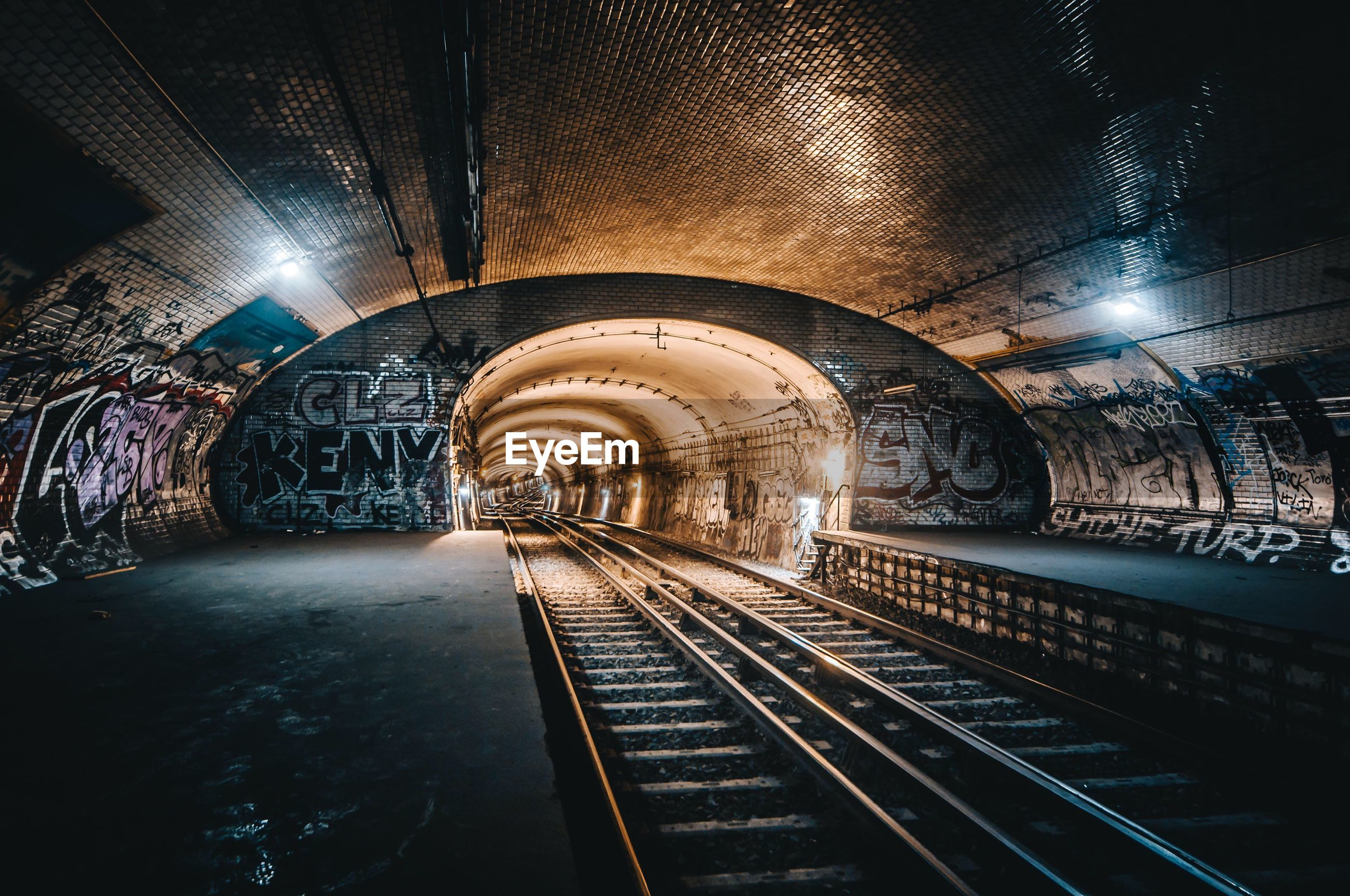 architecture, rail transportation, transportation, illuminated, arch, public transportation, tunnel, railroad track, built structure, the way forward, diminishing perspective, track, indoors, no people, direction, subway, lighting equipment, vanishing point, mode of transportation, wall - building feature, long, ceiling