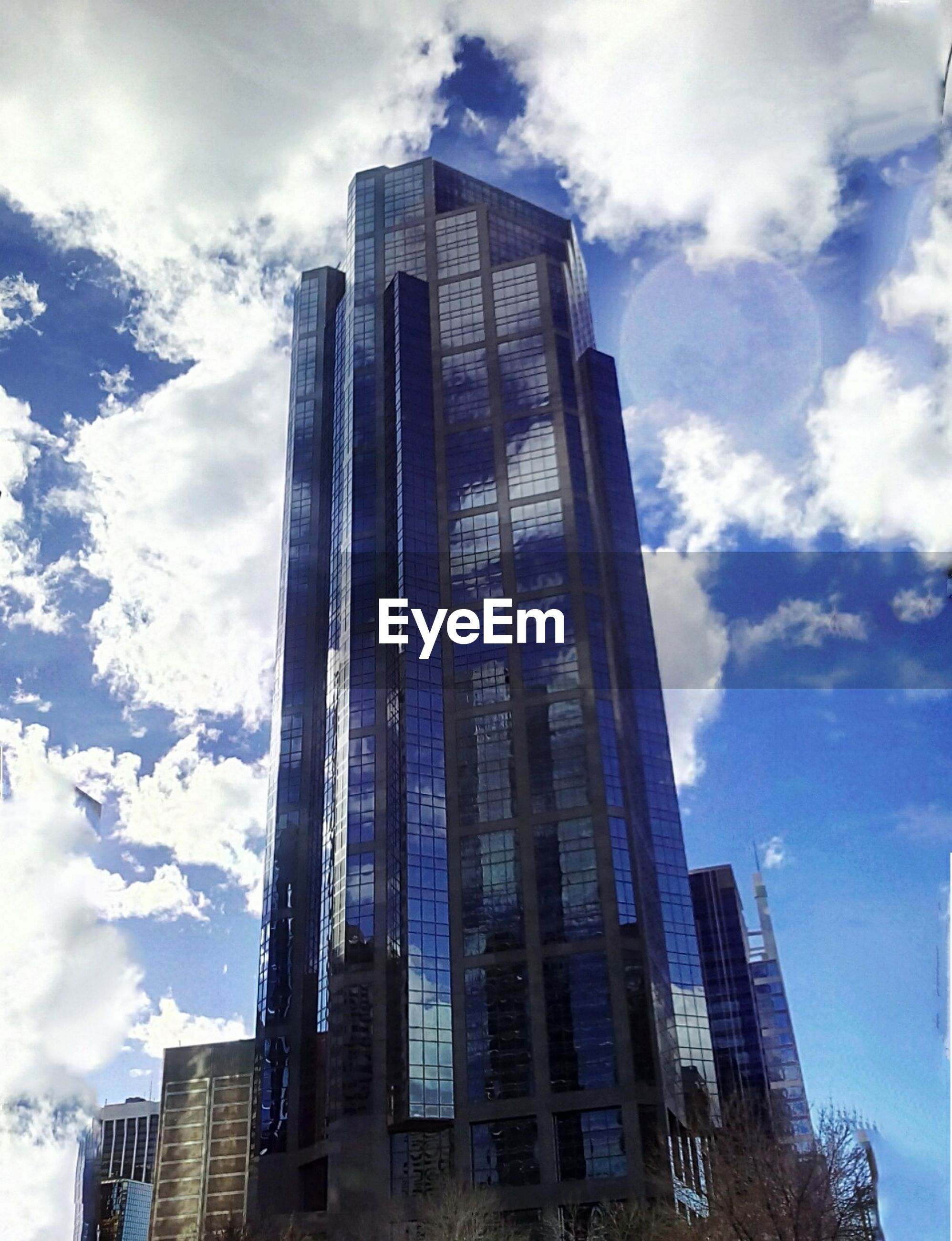 building exterior, architecture, built structure, skyscraper, modern, office building, city, tall - high, low angle view, tower, sky, cloud - sky, glass - material, building, tall, reflection, financial district, cloud, city life, urban skyline