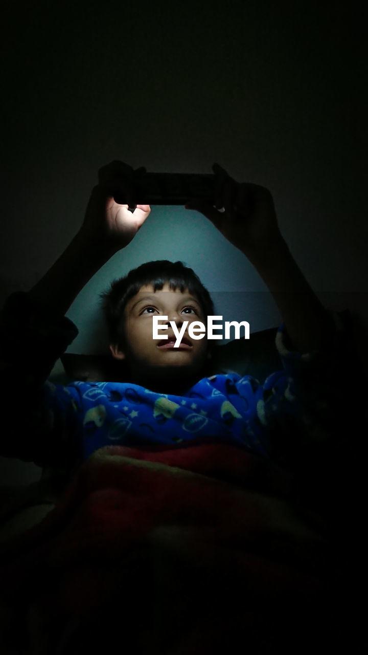Boy Using Phone While Lying In Darkroom