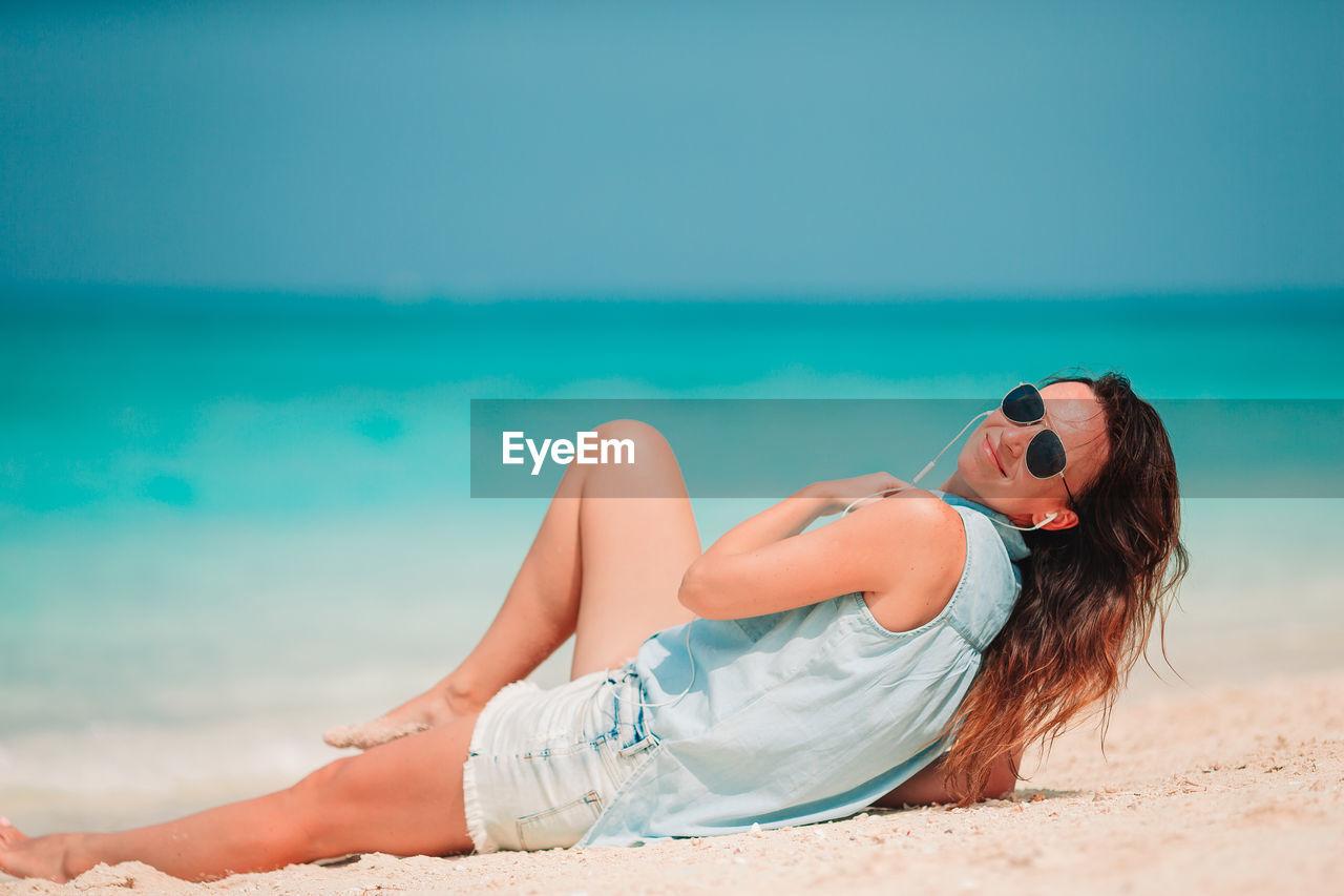 Woman wearing sunglasses sitting on beach