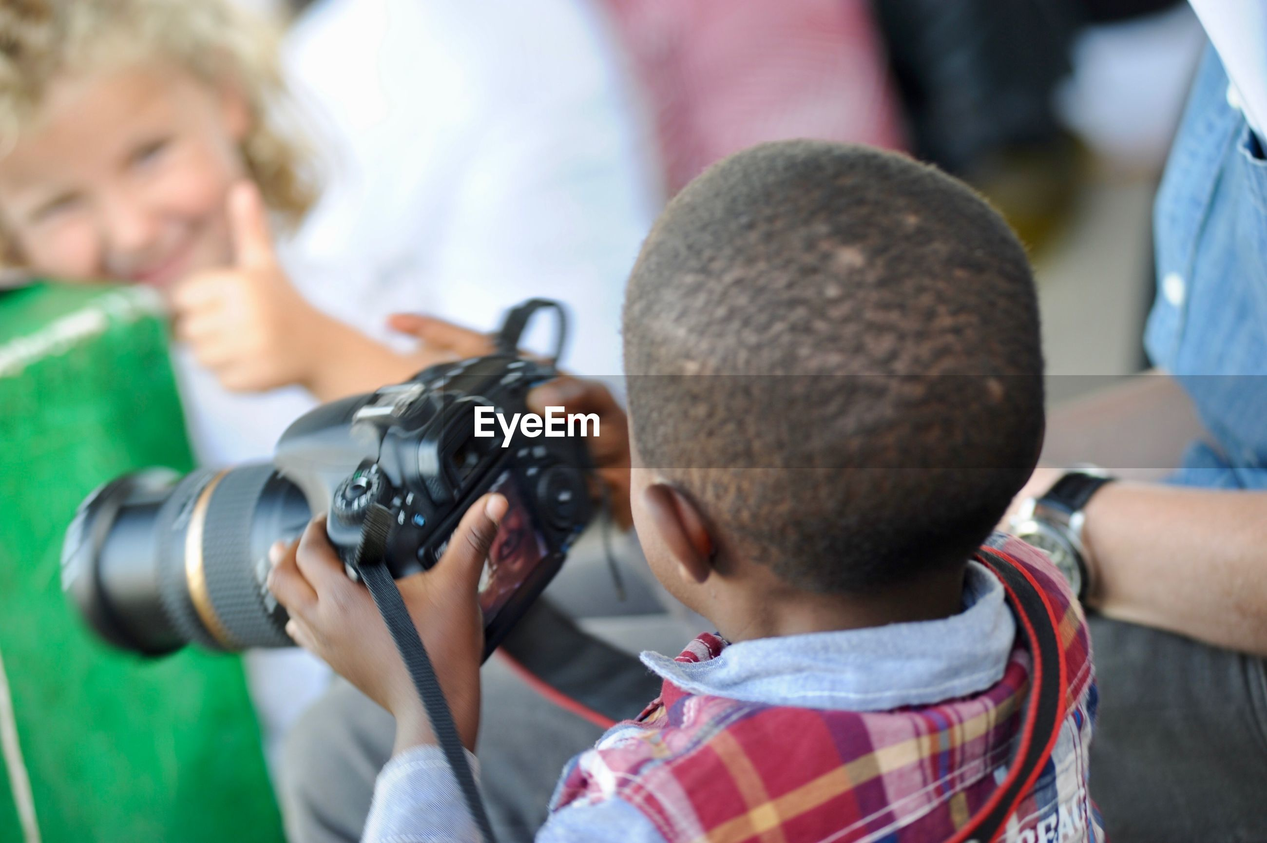 Rear view of boy photographing girl from camera