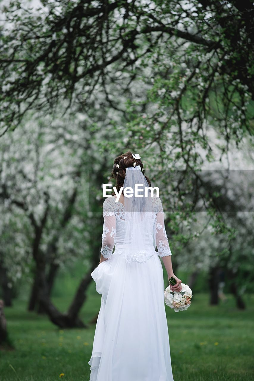 Rear View Of Bride Standing Against Trees On Field
