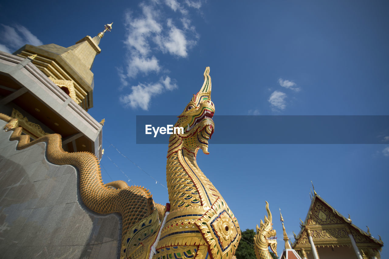 statue, religion, architecture, spirituality, place of worship, sculpture, low angle view, built structure, building exterior, history, sky, day, outdoors, travel destinations, no people, gold colored, dragon, chinese dragon