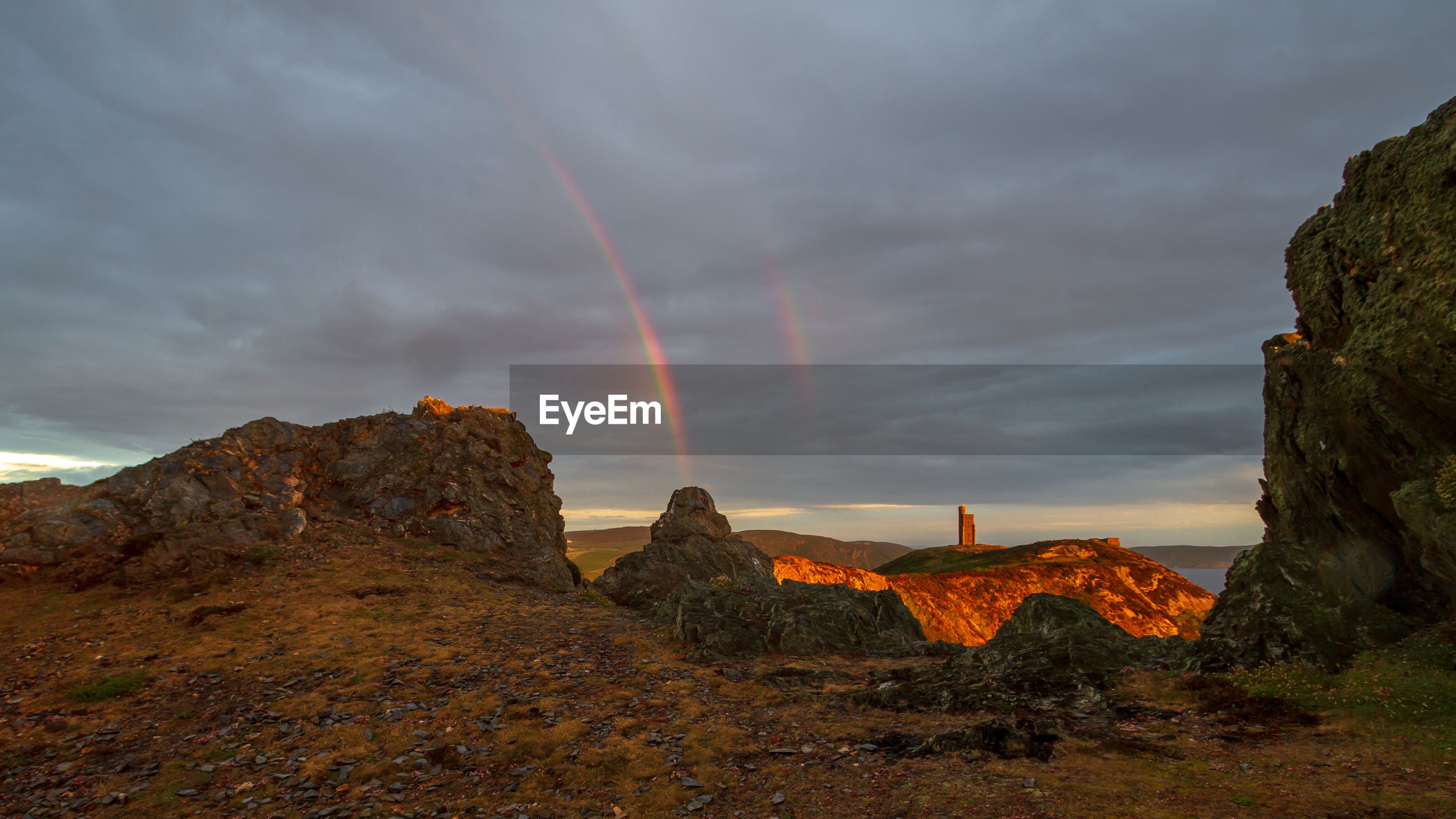 SCENIC VIEW OF RAINBOW OVER ROCKS AGAINST SKY