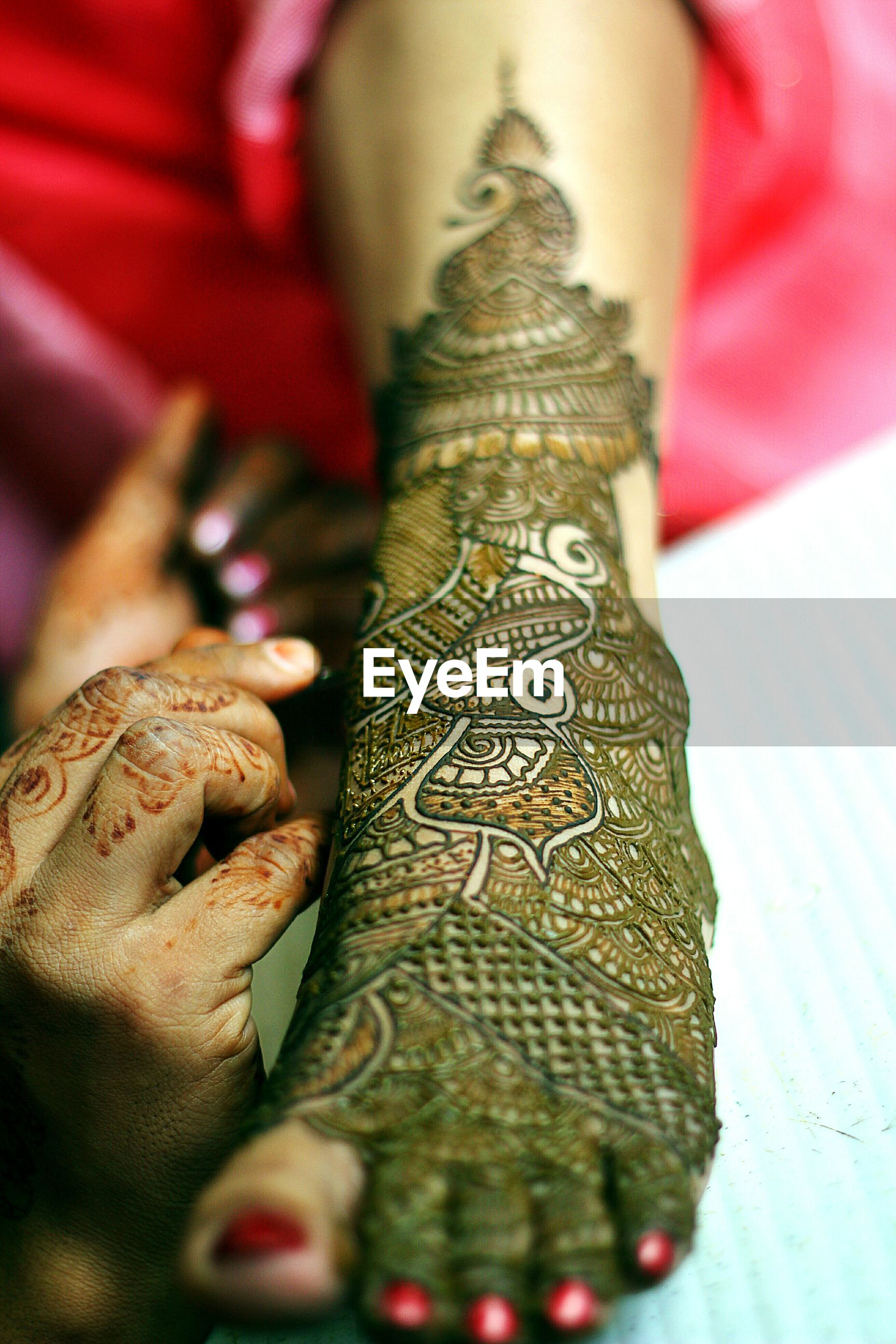 Cropped hand of mehendi artist applying henna tattoo on brides foot