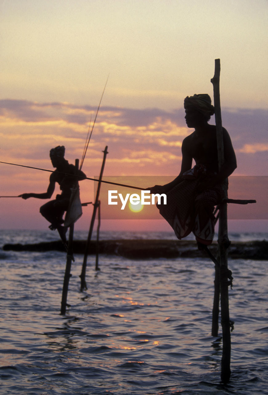 sunset, sky, water, silhouette, real people, sea, waterfront, men, orange color, leisure activity, nature, lifestyles, beauty in nature, activity, standing, occupation, two people, people, full length, outdoors, fisherman