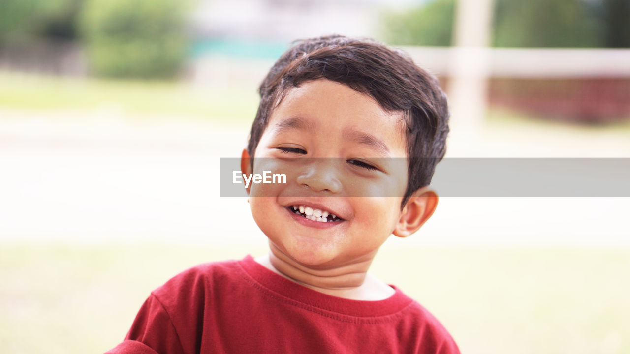 portrait, childhood, child, headshot, boys, smiling, males, one person, front view, happiness, men, focus on foreground, emotion, innocence, close-up, looking at camera, day, casual clothing, real people, outdoors, human face, gap toothed, mouth open