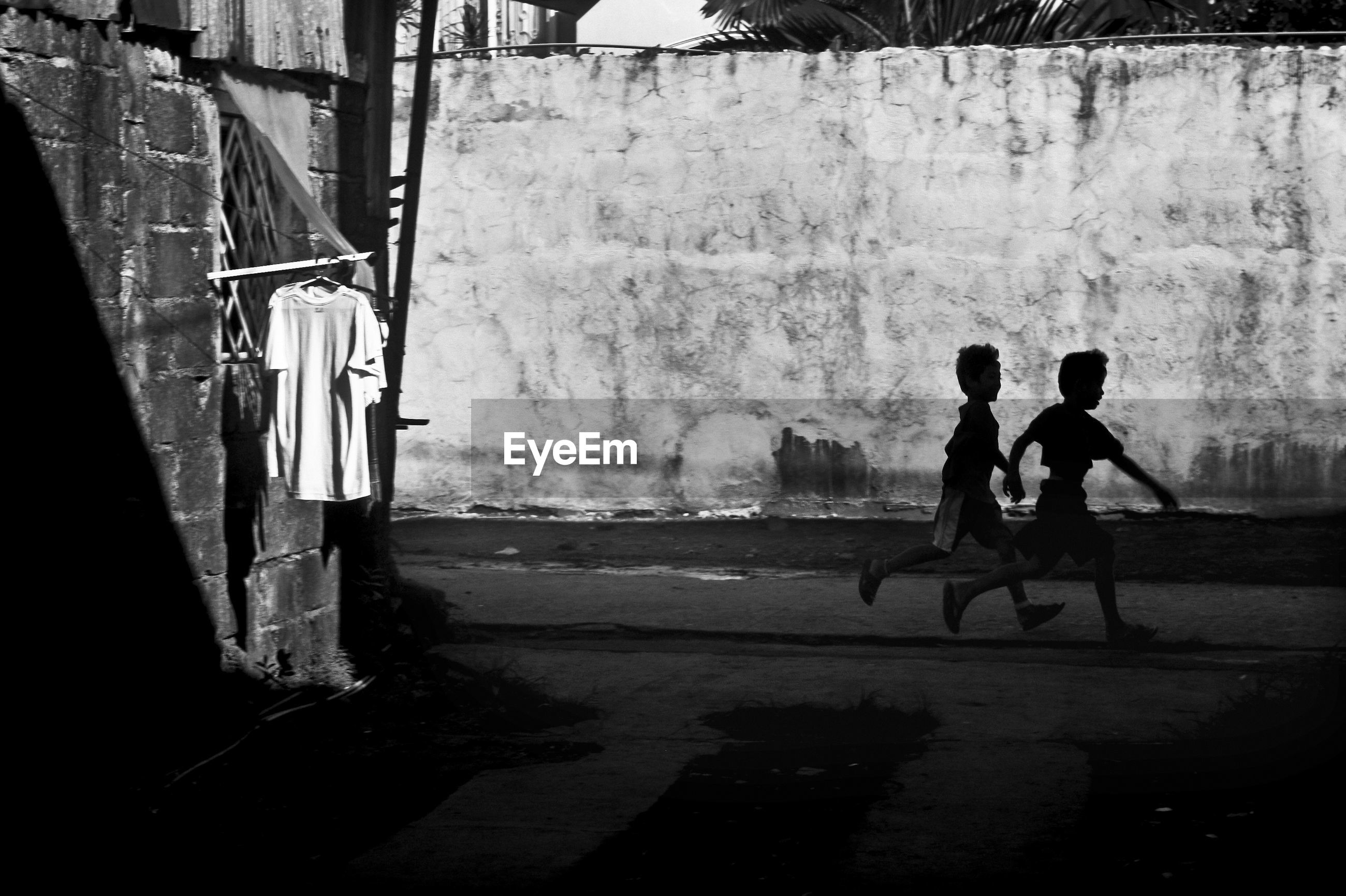 Side view of children running on road