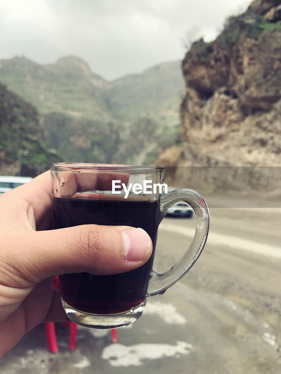 human hand, drink, hand, cup, human body part, refreshment, mug, food and drink, mountain, one person, holding, coffee, real people, day, coffee cup, lifestyles, coffee - drink, focus on foreground, hot drink, finger, body part, mountain range, glass, outdoors, tea cup