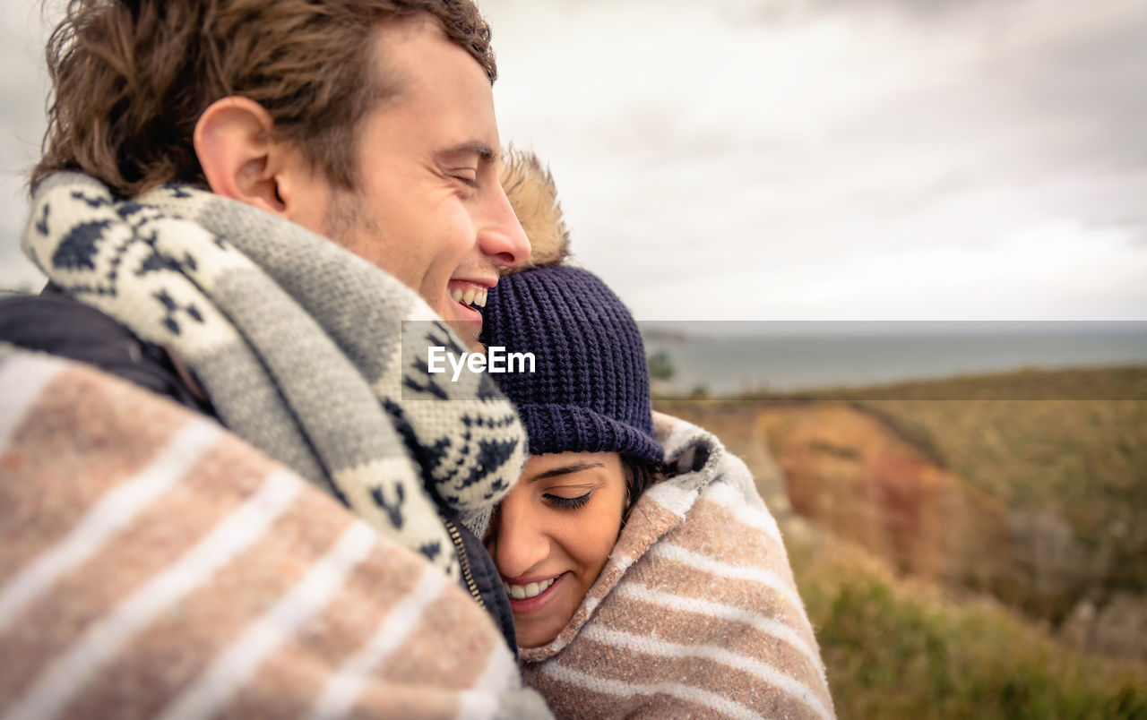 two people, togetherness, emotion, bonding, child, love, sky, lifestyles, leisure activity, positive emotion, family, casual clothing, childhood, real people, happiness, men, smiling, women, males, warm clothing, son