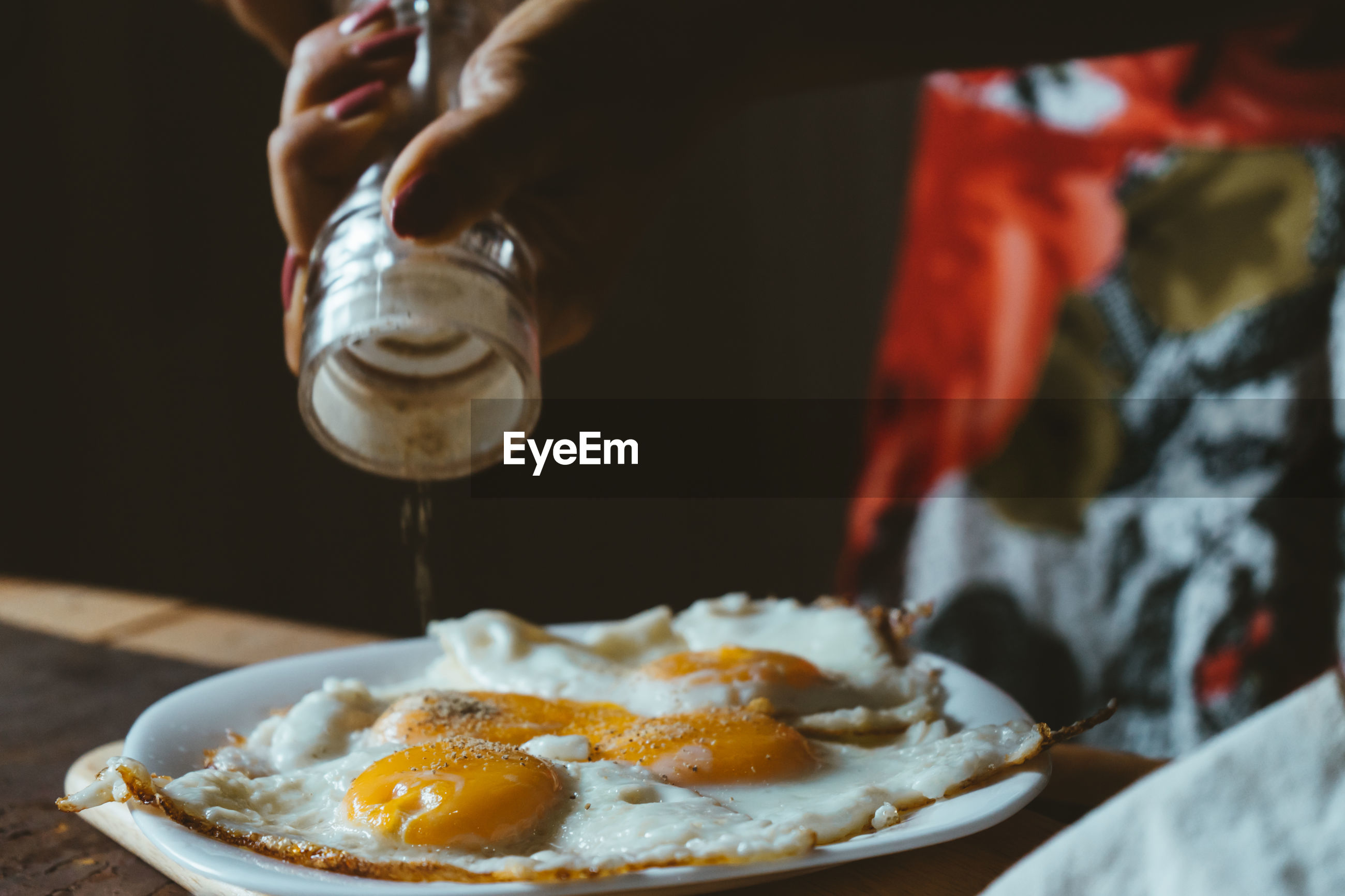Cropped hands of woman sprinkling pepper on fried eggs at home