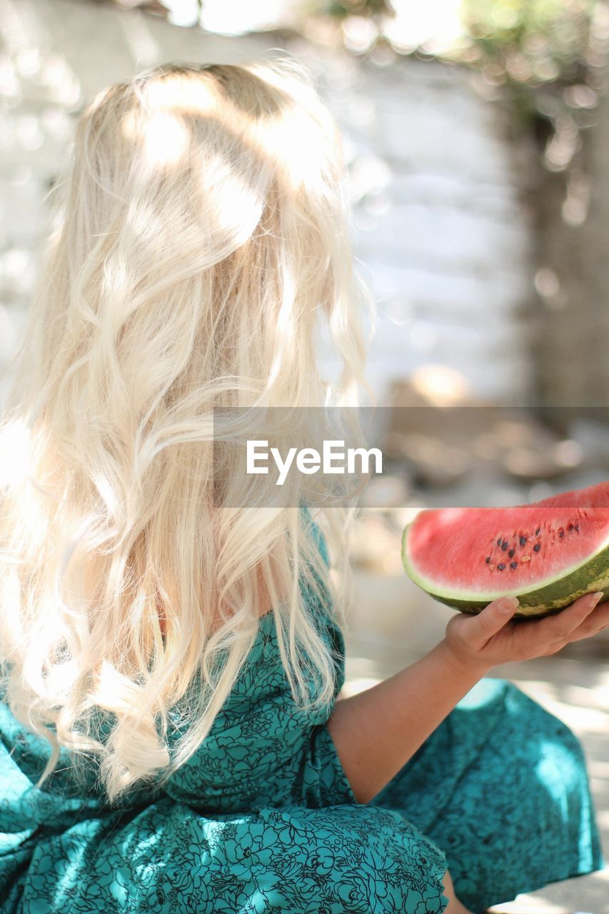 Rear View Of Woman Holding Watermelon Outdoors