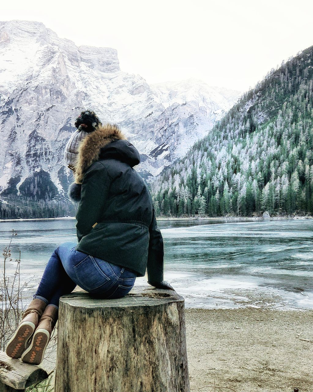 sitting, mountain, snow, nature, winter, day, lake, cold temperature, beauty in nature, one person, leisure activity, water, full length, outdoors, warm clothing, scenics, real people, vacations, tree, young adult, sky, people