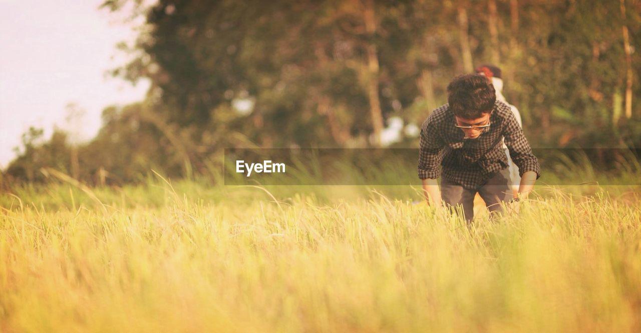 Man Bending Down In Field