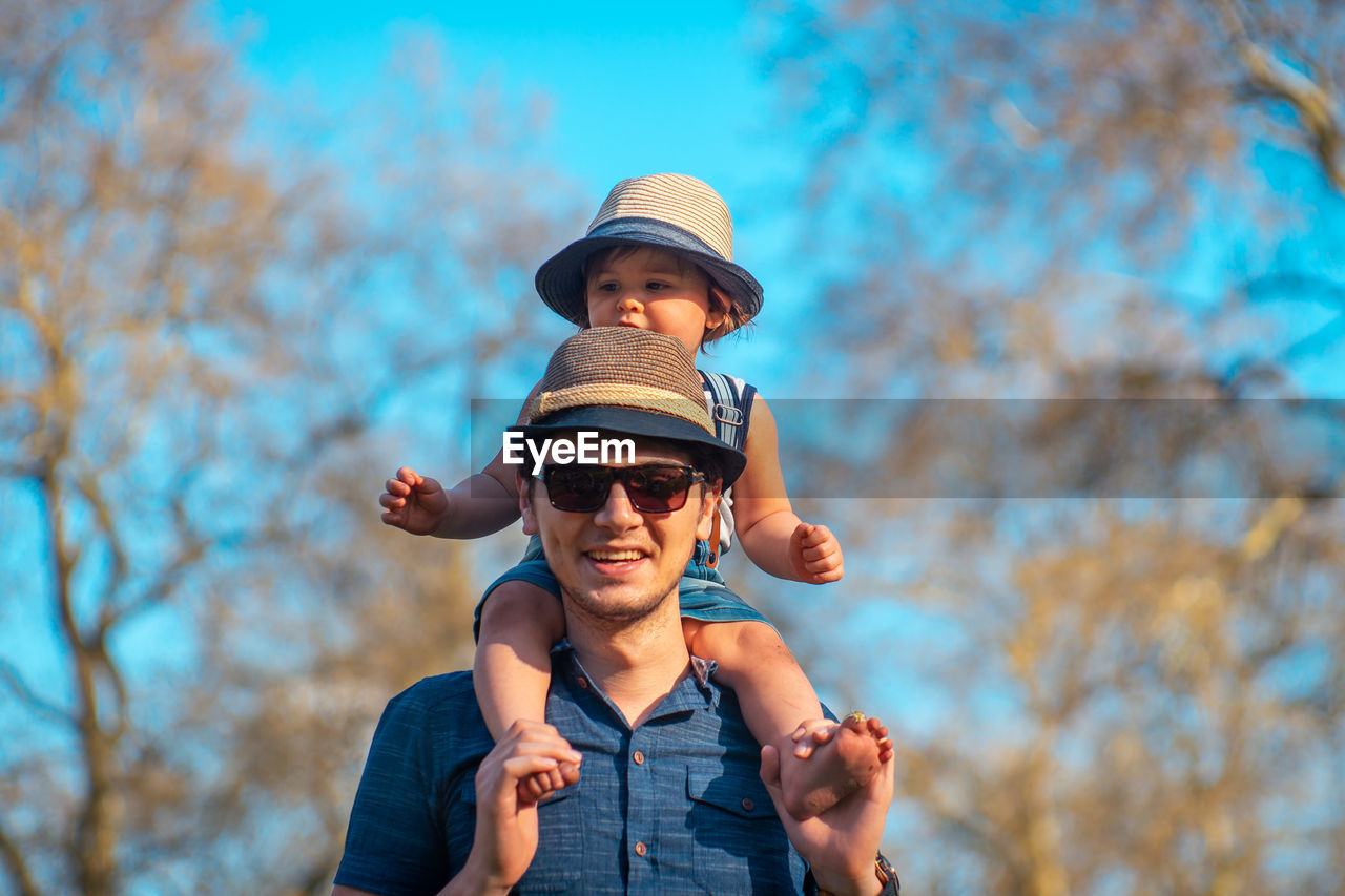 Portrait of father carrying daughter on shoulders against bare trees