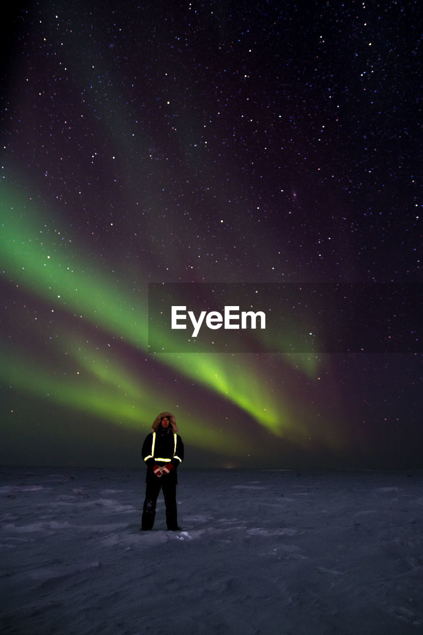 Full Length Of Man Standing On Snow Covered Landscape Against Aurora Borealis