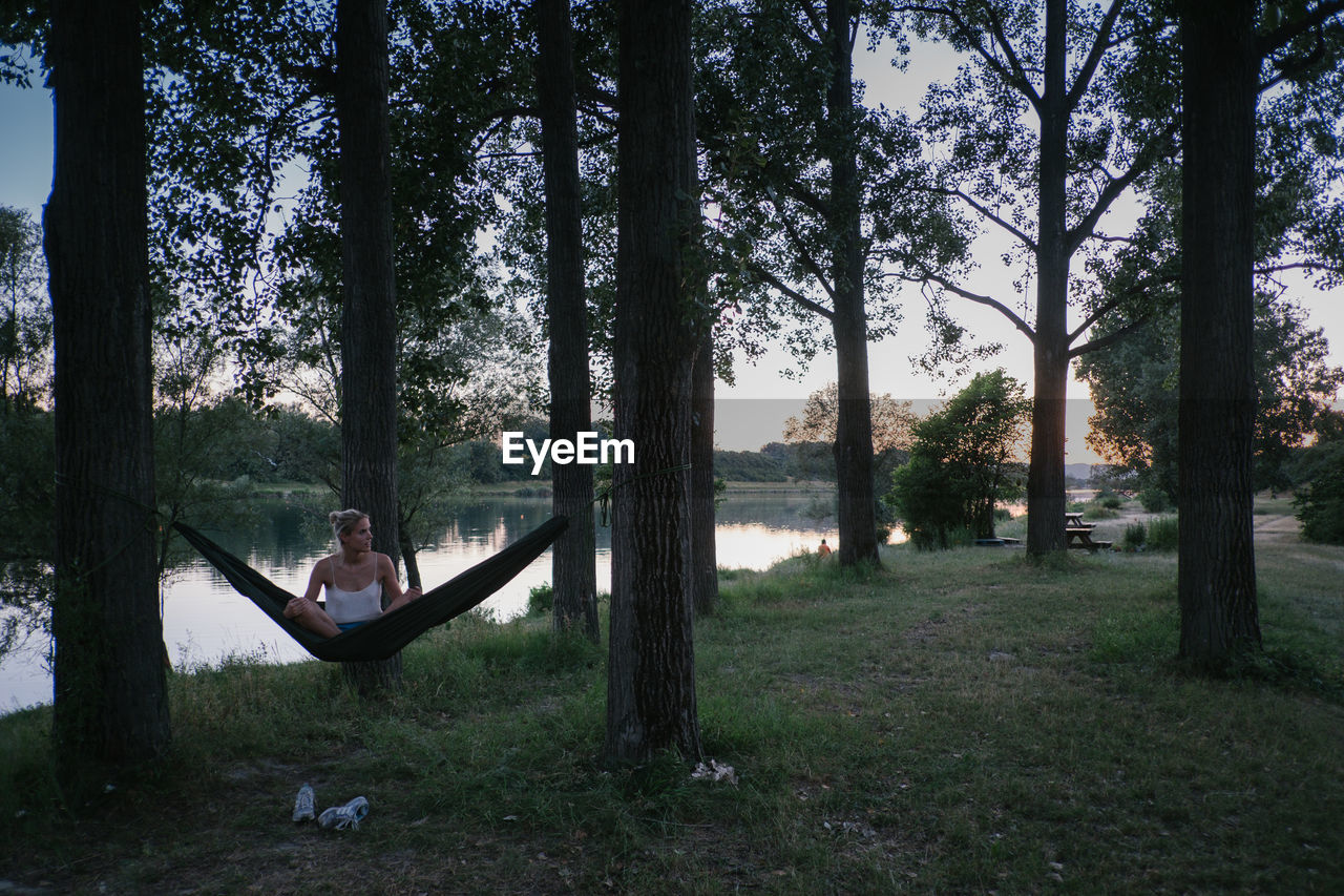 Young Woman Sitting On Hammock Amidst Trees By Lake