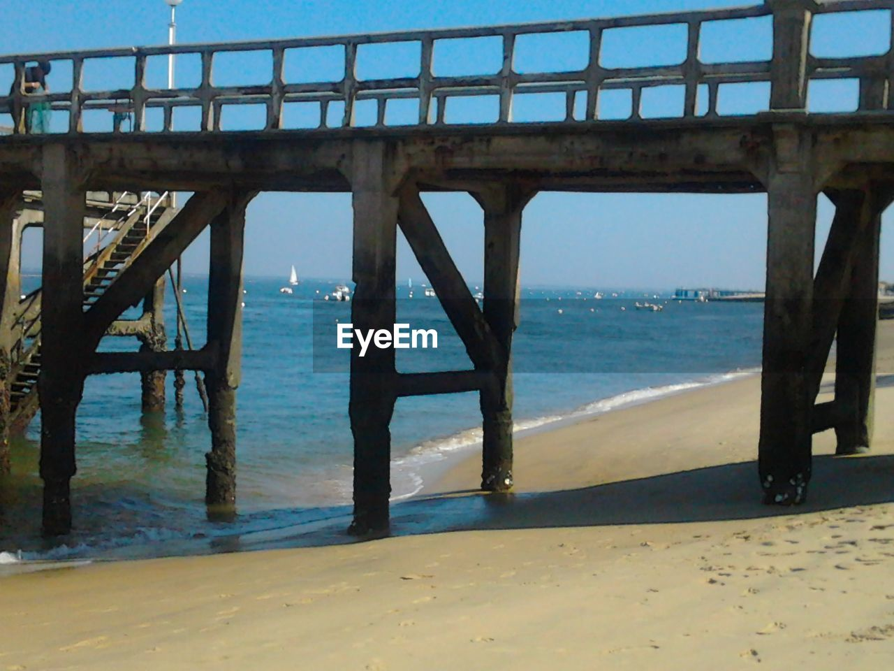 sea, bridge - man made structure, built structure, horizon over water, water, architecture, connection, beach, pier, day, nature, sunlight, scenics, sand, sky, outdoors, architectural column, underneath, no people, blue, girder