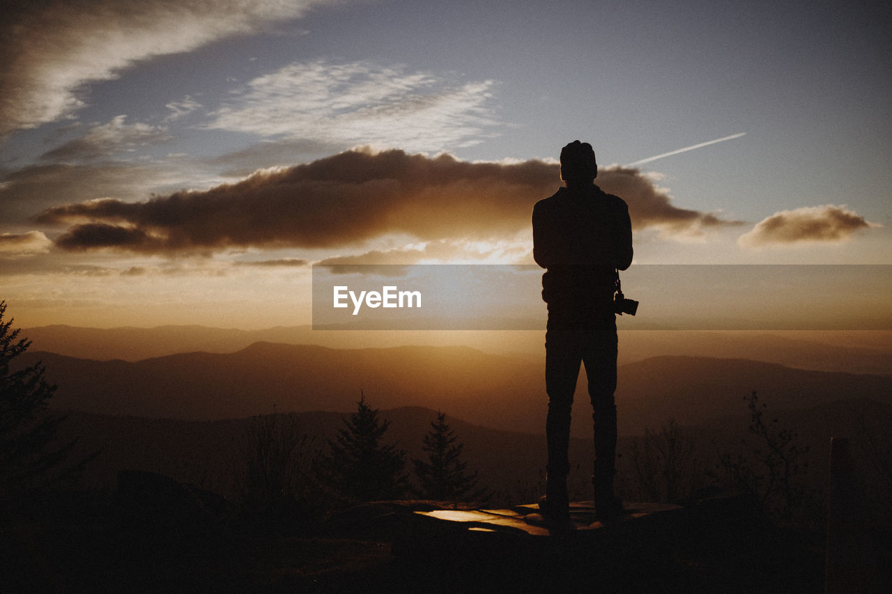 Rear view of silhouette man standing at mountain against sky during sunset