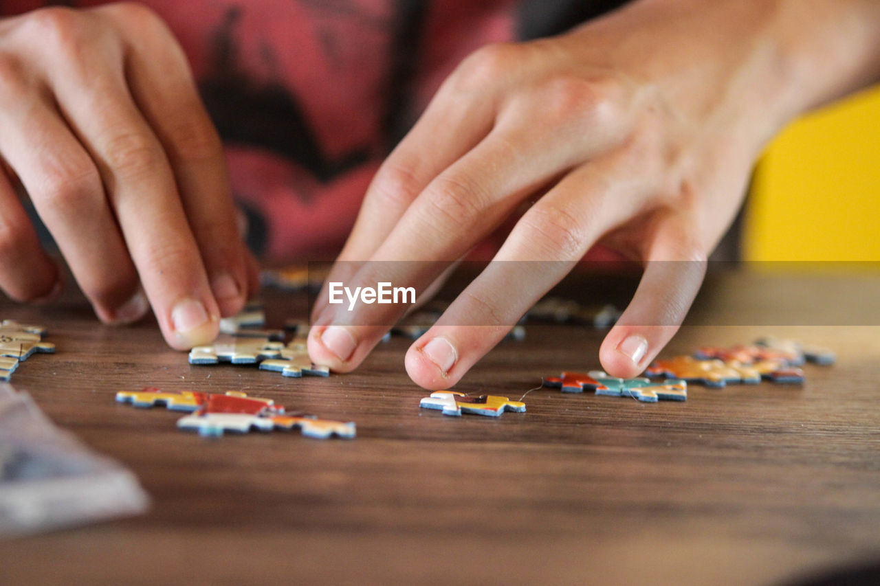 human hand, hand, human body part, leisure activity, table, selective focus, indoors, real people, leisure games, people, playing, wood - material, lifestyles, relaxation, men, arts culture and entertainment, game, toy, two people, finger, human limb