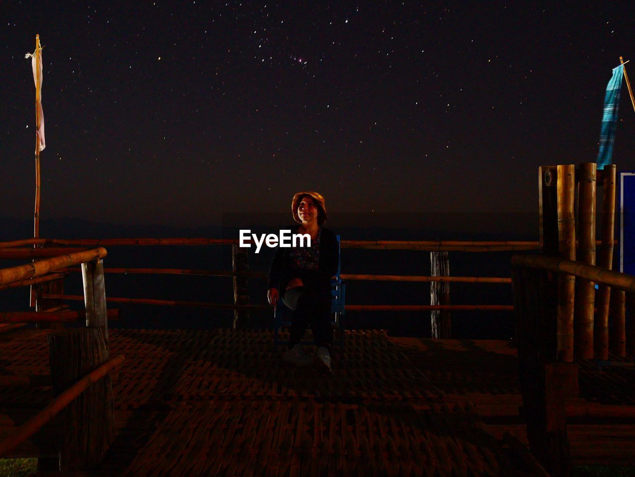 WOMAN SITTING ON SEAT AT NIGHT
