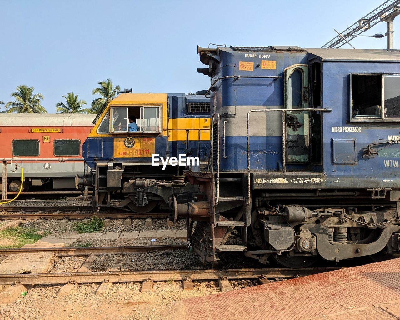TRAIN ON RAILROAD TRACKS AGAINST CLEAR SKY