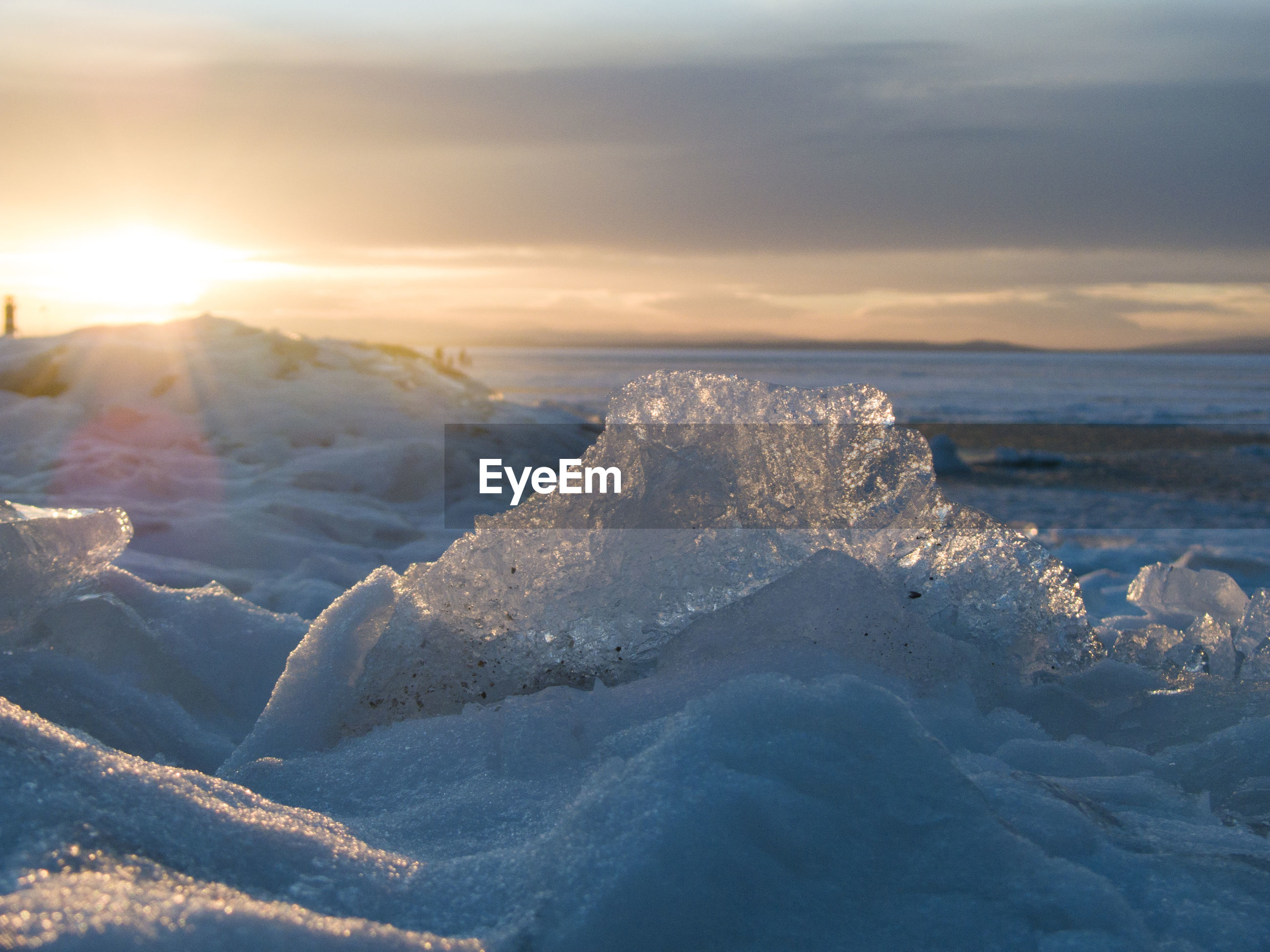 Close-up of ice at frozen lake neusiedl against sky during sunset