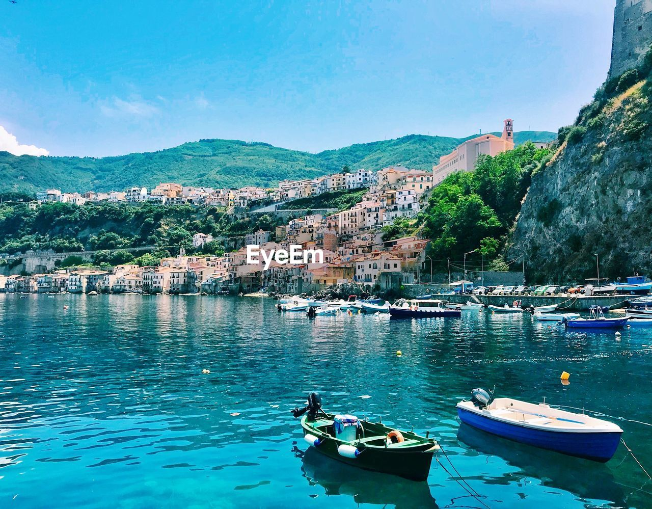 Sailboats moored in sea by townscape against sky