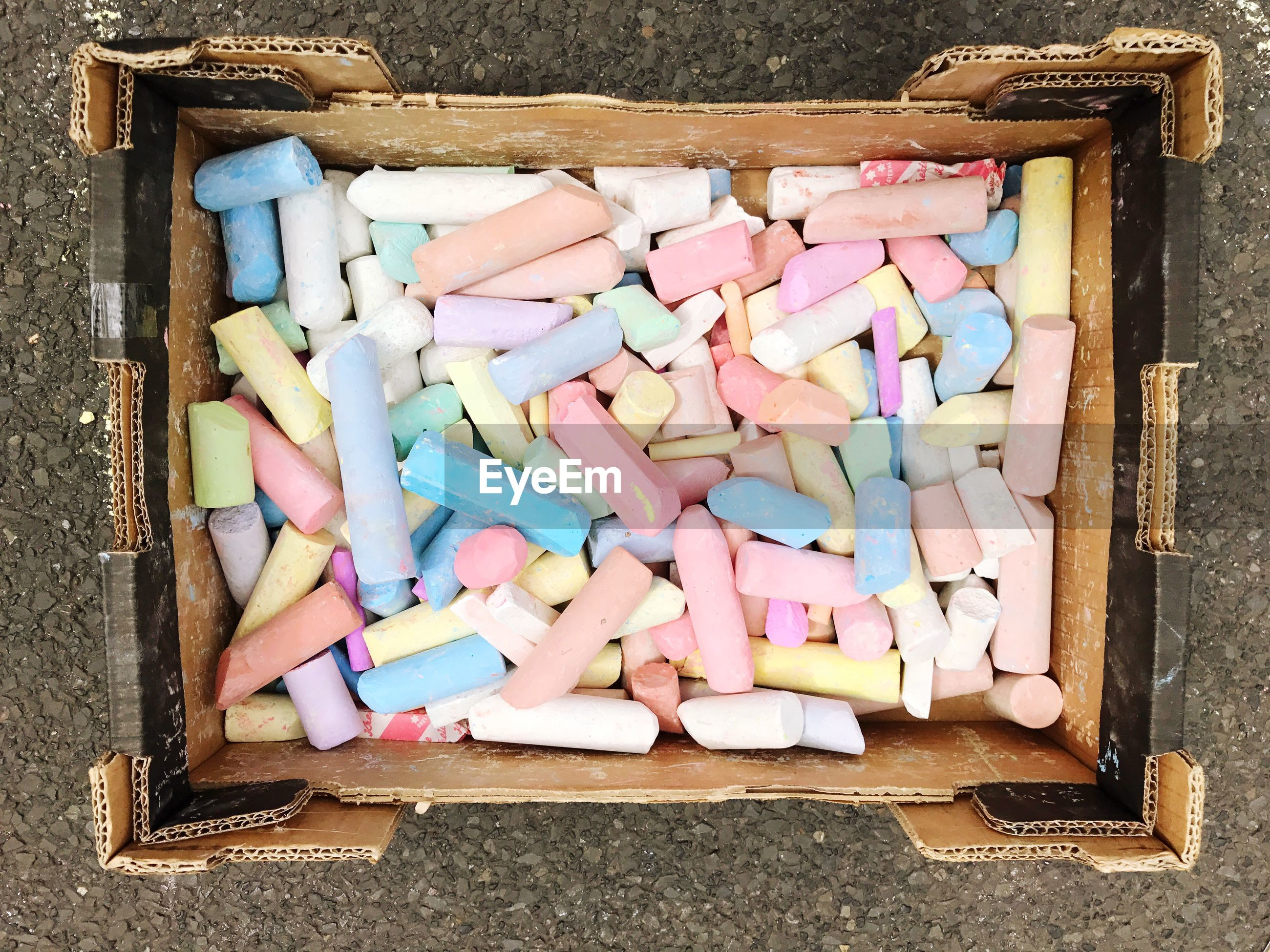 Directly above shot of colorful chalks in cardboard box