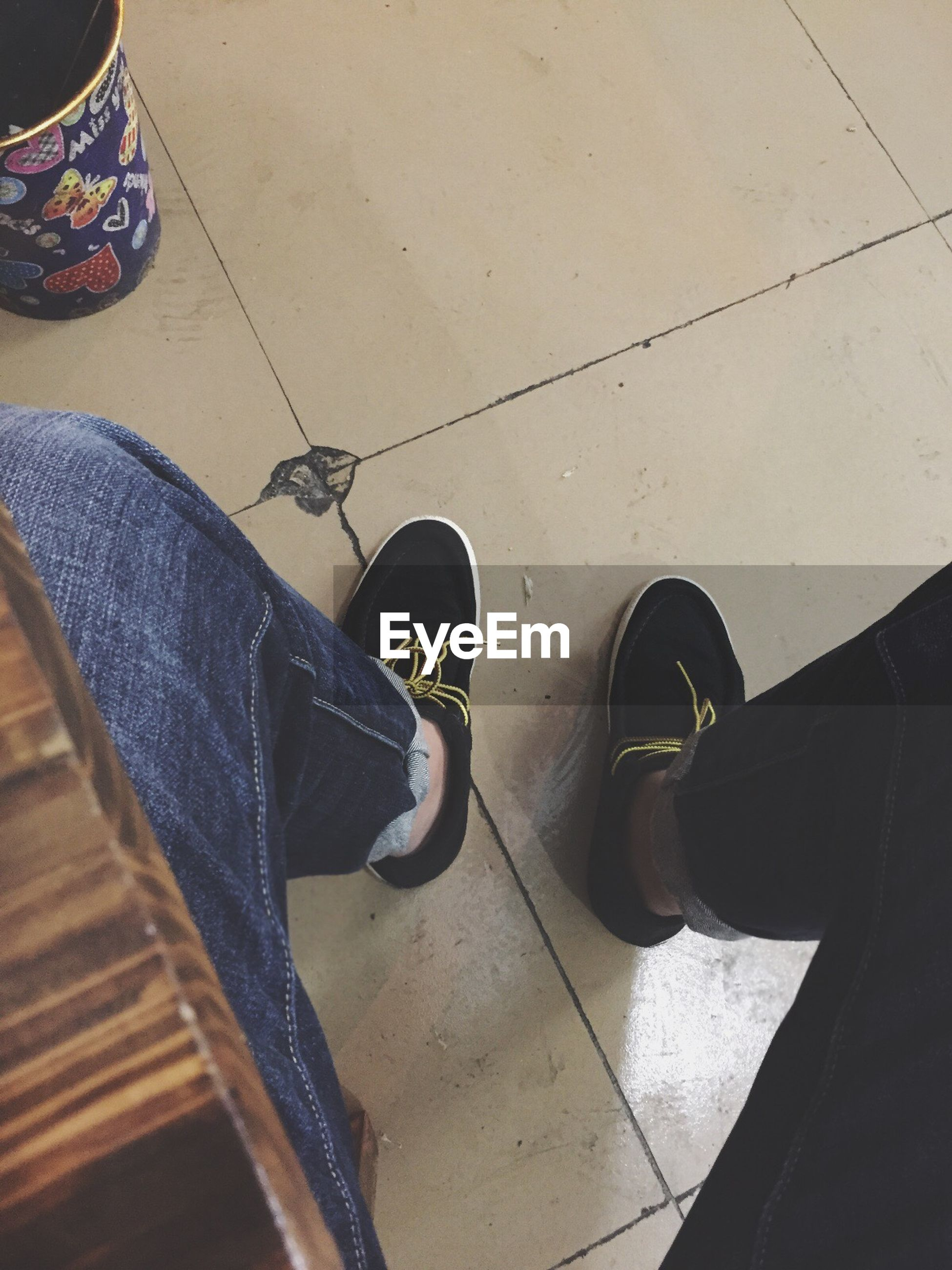 low section, shoe, person, high angle view, indoors, footwear, standing, jeans, human foot, personal perspective, lifestyles, flooring, chair, men, day, canvas shoe, sunlight