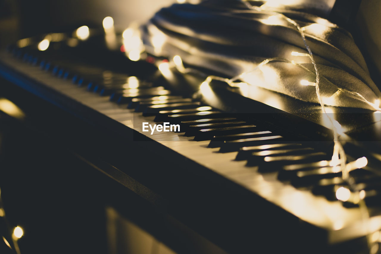 indoors, selective focus, close-up, music, musical instrument, musical equipment, piano, no people, illuminated, piano key, in a row, candle, arts culture and entertainment, focus on foreground, still life, celebration, lens flare, pattern, white color, glowing, keyboard instrument