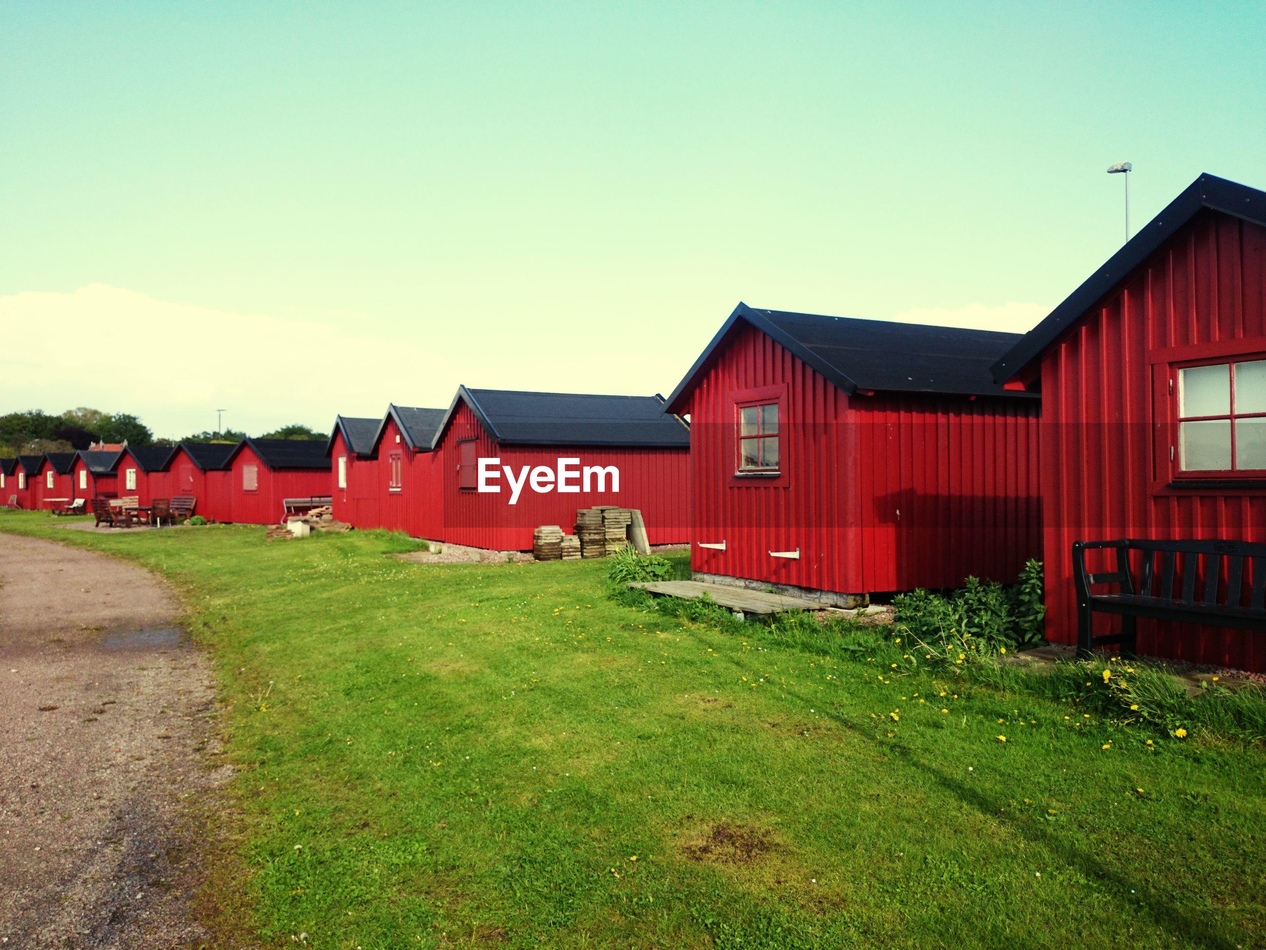 HOUSES ON GRASSY FIELD AGAINST SKY