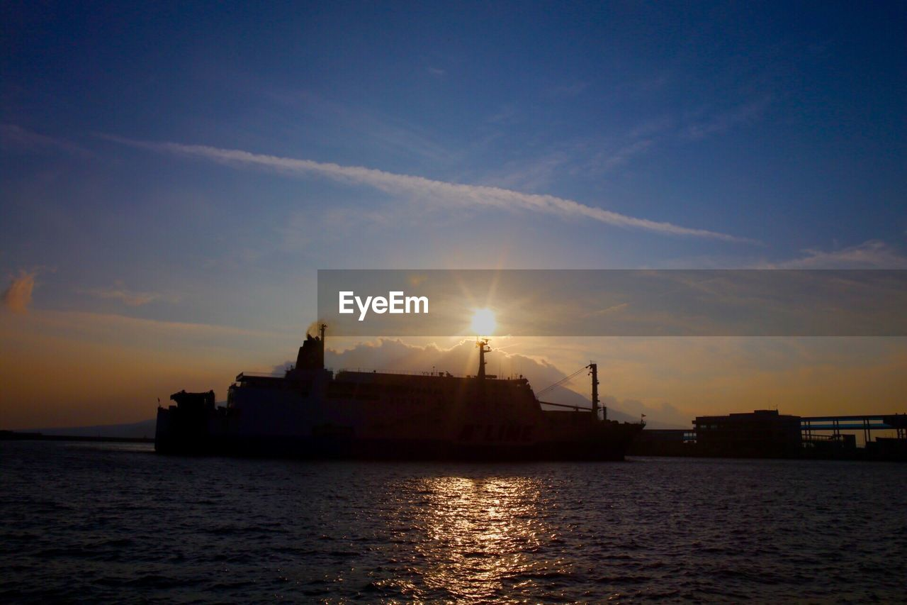 sunset, nautical vessel, waterfront, sea, water, sky, sun, transportation, silhouette, lens flare, tranquility, beauty in nature, sunlight, nature, scenics, outdoors, architecture, no people, tranquil scene, building exterior, travel destinations, cloud - sky, built structure, harbor, sailing, day, offshore platform, drilling rig