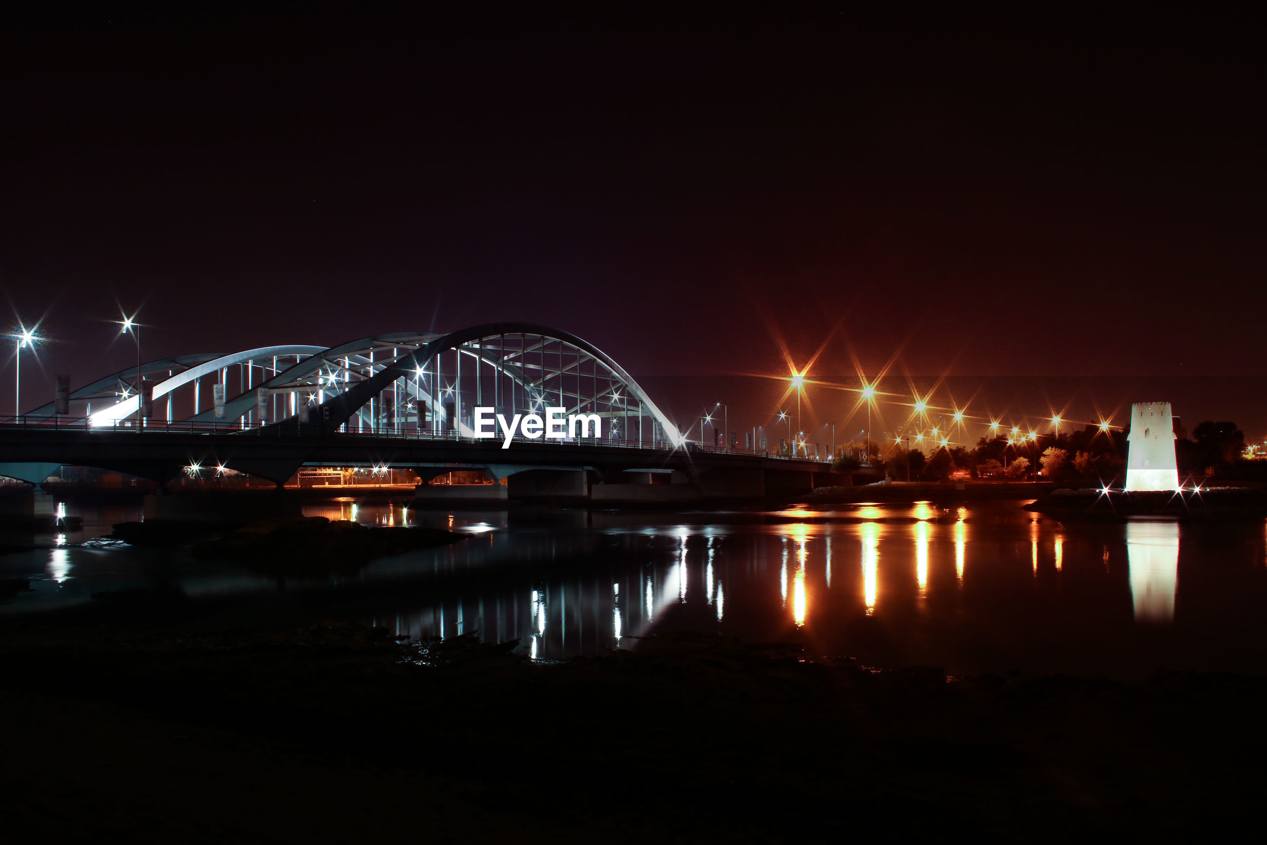 ILLUMINATED BRIDGE OVER RIVER AGAINST SKY
