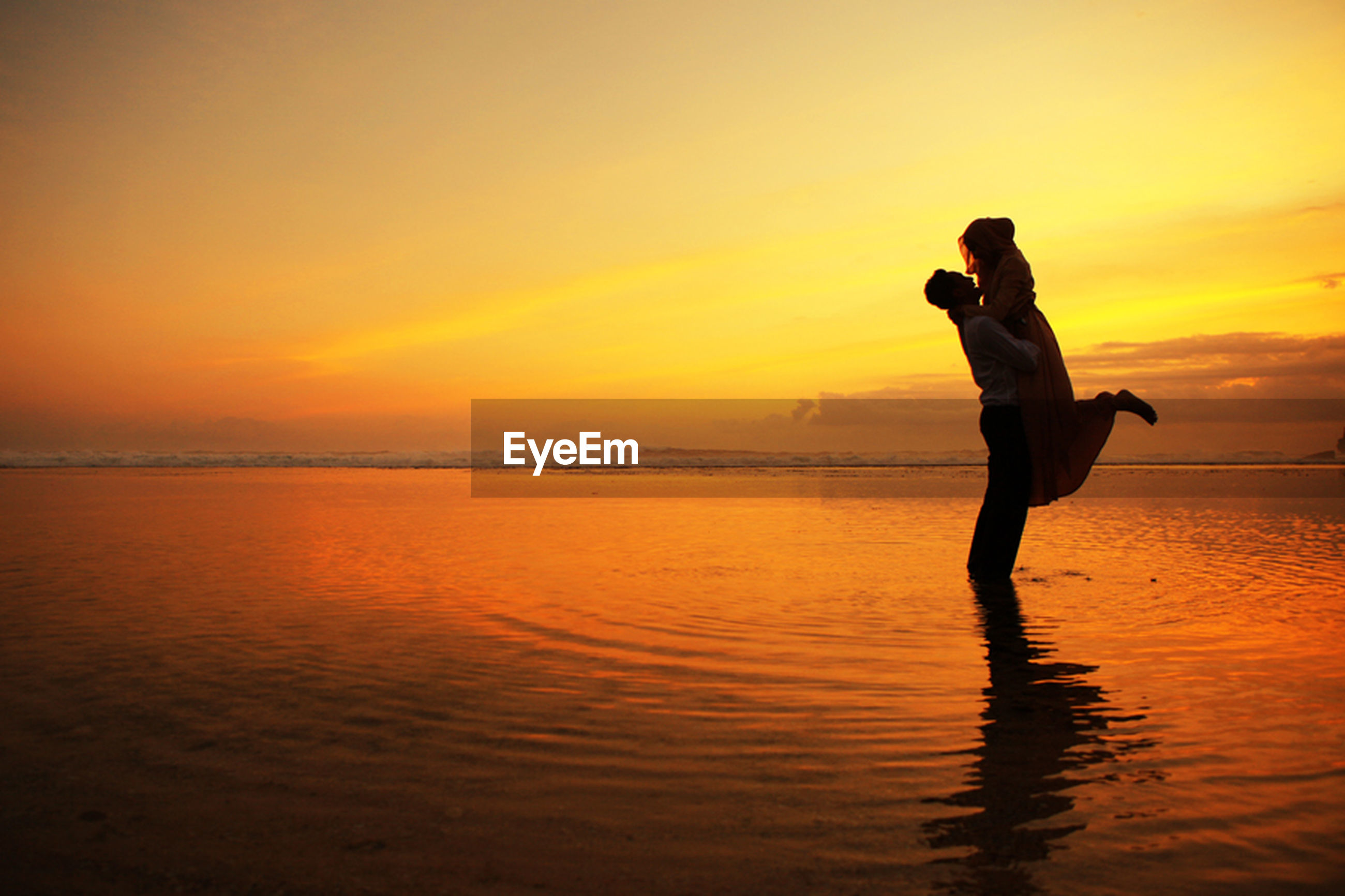sunset, water, sea, silhouette, leisure activity, horizon over water, orange color, lifestyles, beach, sky, scenics, standing, vacations, tranquil scene, beauty in nature, reflection, tranquility, idyllic