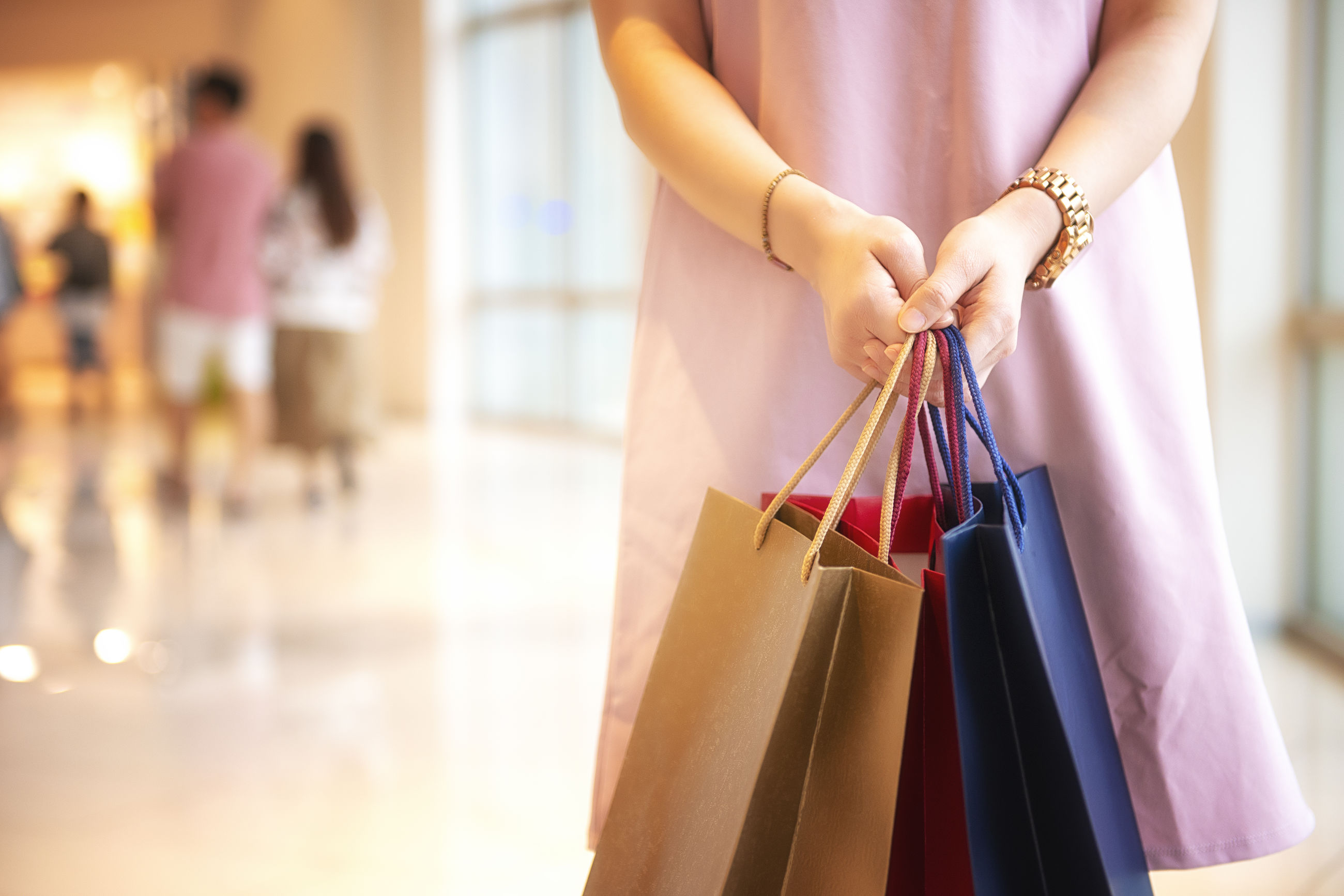Midsection of woman holding shopping bags in mall